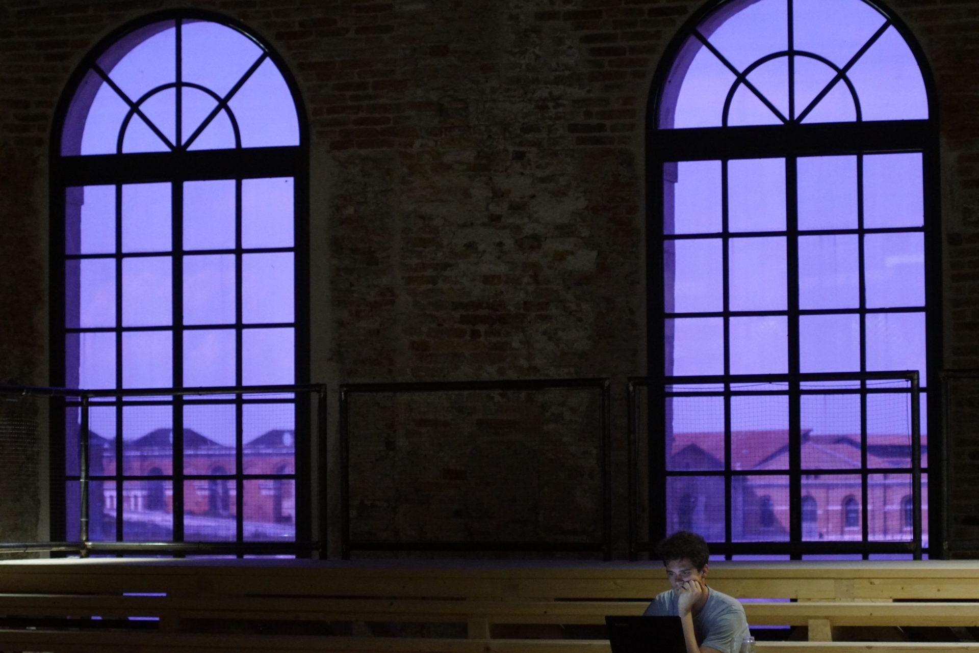 Zwei große lila Rundbogenfenster durch die man Teile des Arsenals von Venedig sieht. Im Vordeergrund sind lange helle Tische zu sehen an denen ein Mann in einen Laptop Blickt