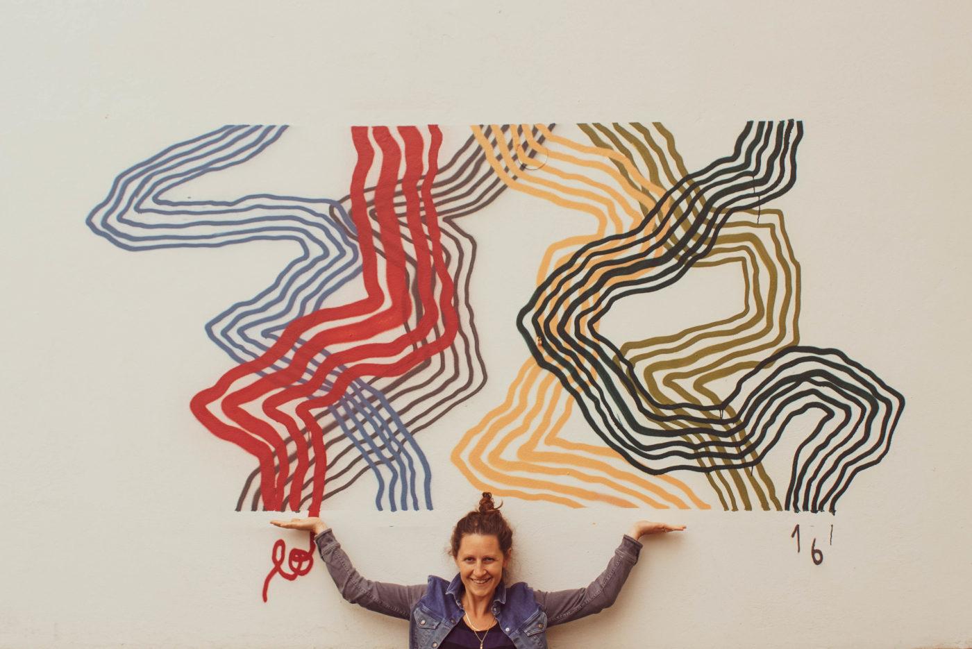 Lea steht vor einer Wand auf der jeweils vier Linien wacklig nach oben führen. Sie hält die Hände geöffnet nach oben, so dass Sie genau mit den Linien abschließen