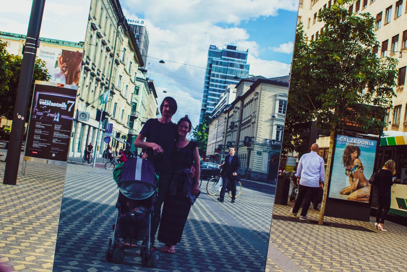 Zu sehen ist die Fußgängerzone von Ljubjana. Wir stehen vor einem Spiegel, so dass wir und die Stadt dahinter bläulich erscheinen.