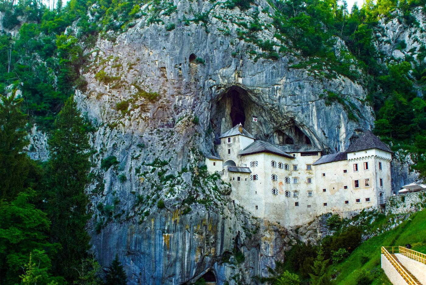Es ist die Höhlenburg Predjama zu sehen wie sie sich an den Felsen schmiegt