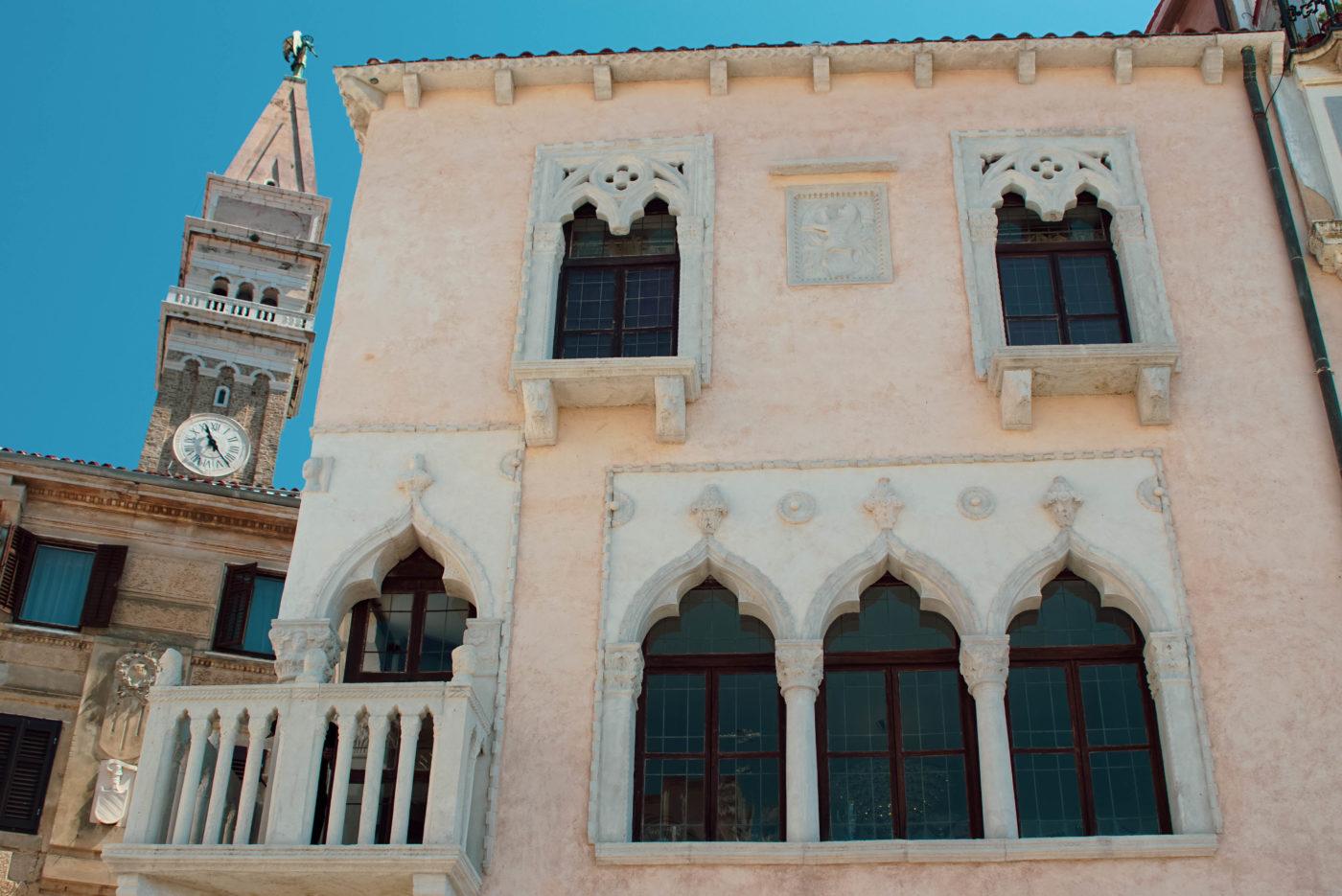 Es ist ein zweistöckiges beiges altes Handelshaus zu sehen. An der Linken Seite gibt es einen Balkon. Fenster Rahmen und Balkon haben orientalische Merkmale und sind aus weißem Marmor gefertigt. Im Hintergrund erhebt sich eine venezianische Kirchturmspitze ähnlich wie die am St. Marcus Platz in Venedig