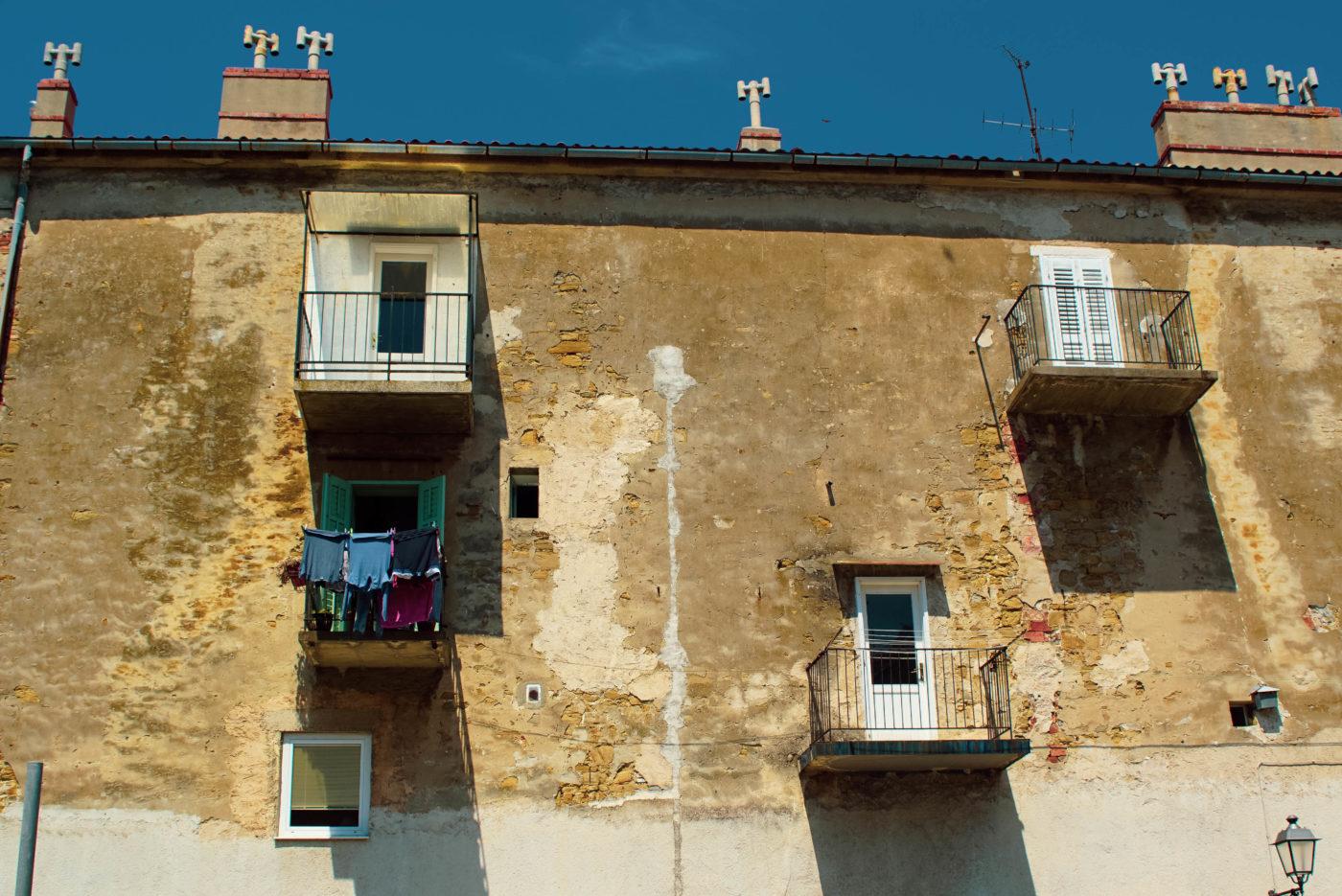 Zu sehen ist ein beige Hauswand von der der Putz bröckelt und dort Backsteine zum Vorschein kommen. Es gibt vier Balkons die alle auf unterschiedlichen Höhen angebracht sind. Alle vier sind unterschiedlich gestaltet, mit verschiedenen Geländern, Türen und in ihrer Größe.