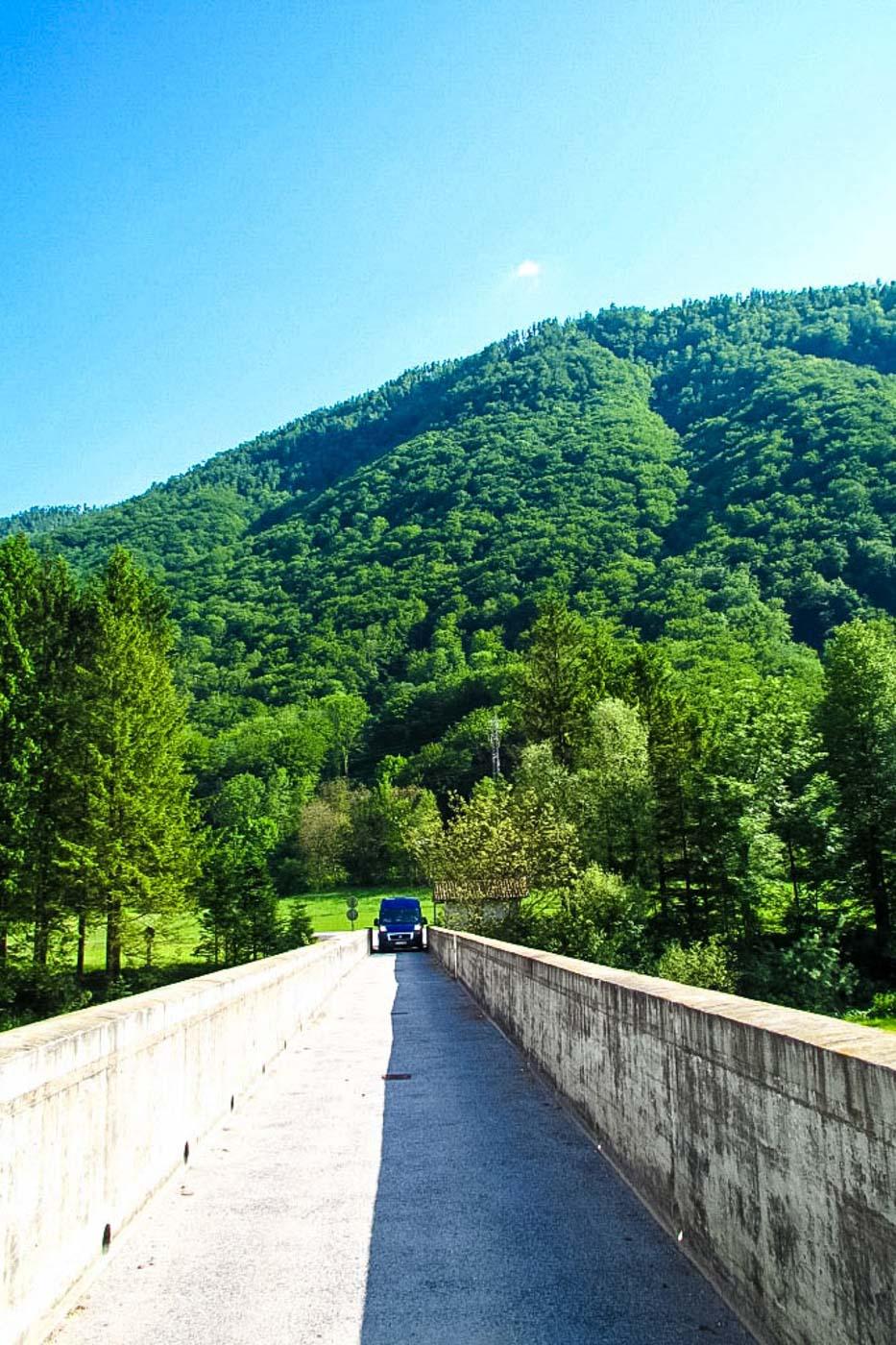 Es ist eine sehr schmale Brücke Brücke zu sehen, über die unser Fiat Ducato fährt und gerade so von der breite über diese fahren kann. Im Hintergrund ist eine tief grün bewachsene Bergflanke zu sehen und darüberr erstreckt sich ein blauer wolkenloser Himmel