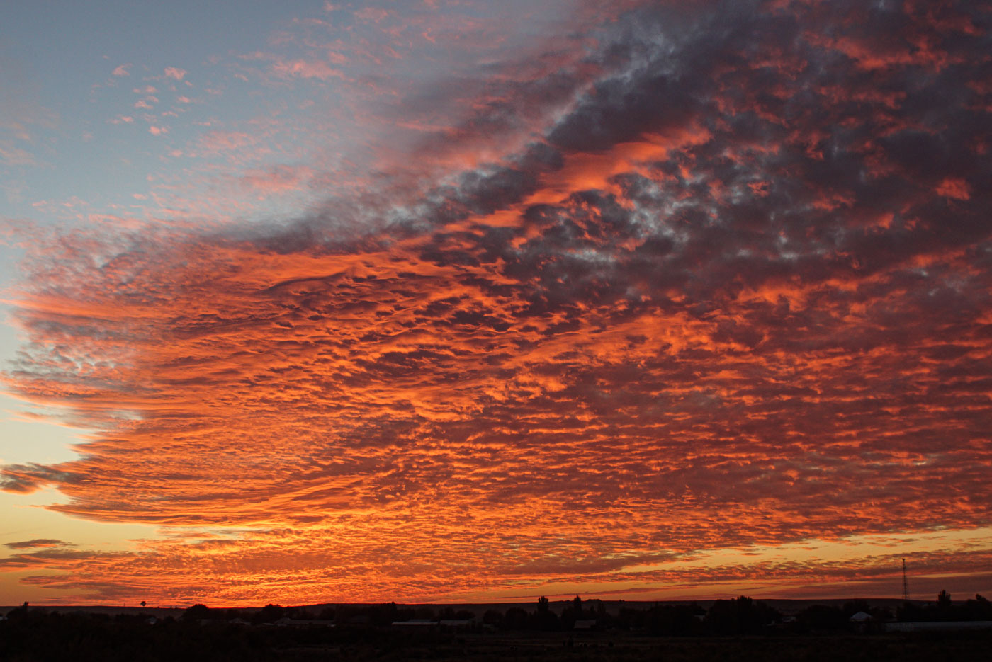 zu sehen sind dichte Wolken Formationen die von unten von der untergehenden Sonne bestrahlt werden sie werden in ein oranges rotes Licht getaucht und bilden so einen spektakulären Anblick.