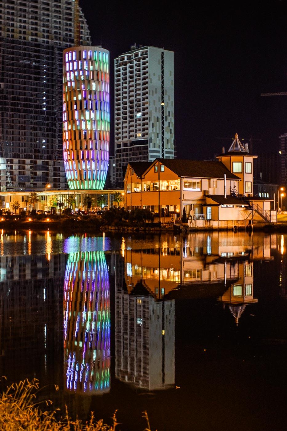 Zu sehen ist die public service Hall, die sich in dem Wasser der tanzenden Fontänen widerspiegelt. Sie ist durch LED Regenbogenfarben erleuchtet. Im Vordergrund ist ein älteres Holzgebäude zu sehen welches einen netten Kontrast bildet.