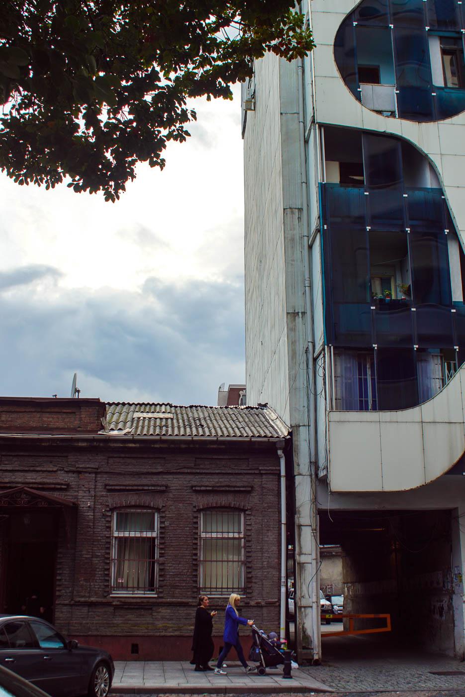 Zu sehen ist ein altes einstöckiges Backsteinhaus, direkt daneben schließt sich ein modernes Wohnhaus mit Glasfassade und Blech Verzierungen an. Im Vordergrund läuft eine Mutter mit Kinderwagen und einer älteren Dame.