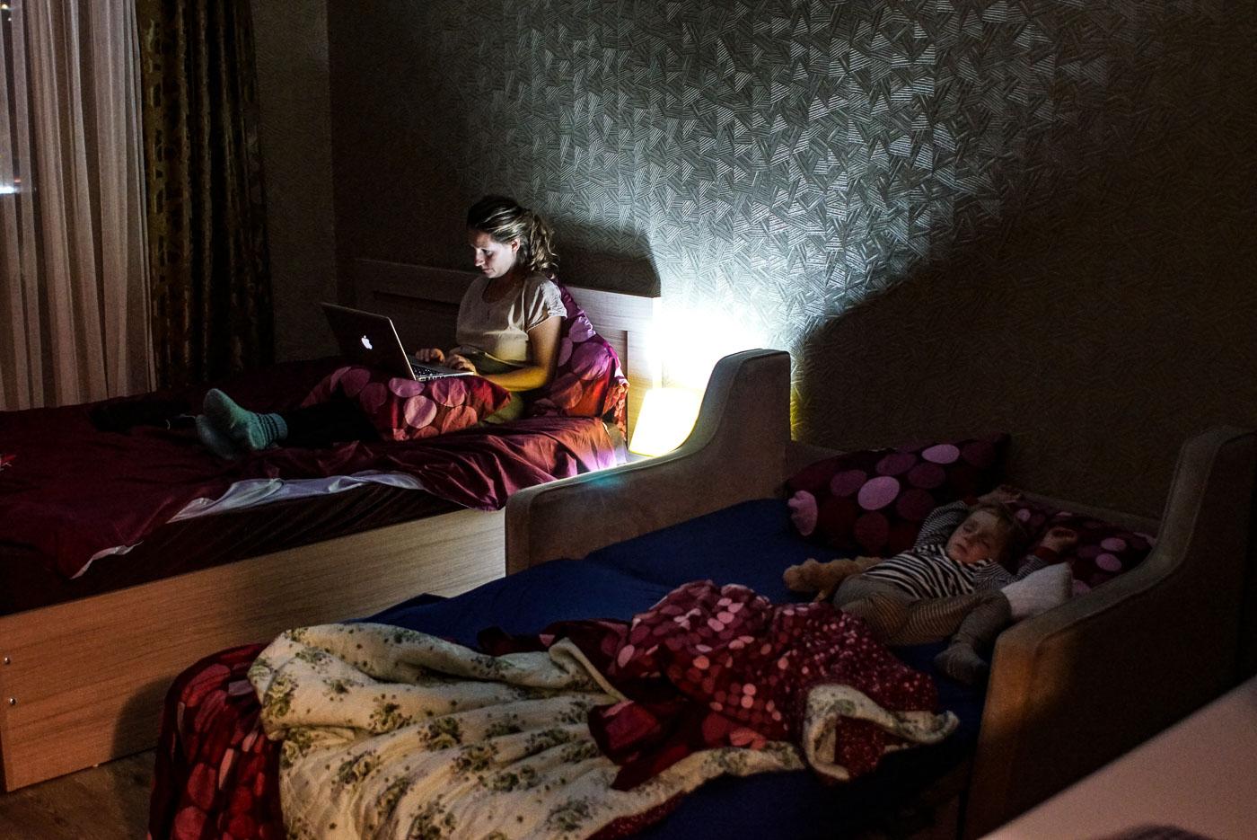 Zu sehen ist, wie Lea in unserem Apartment in Batumi am Laptop Arbeit. Luk liegt daneben auf der Schlafcouch und schläft friedlich.