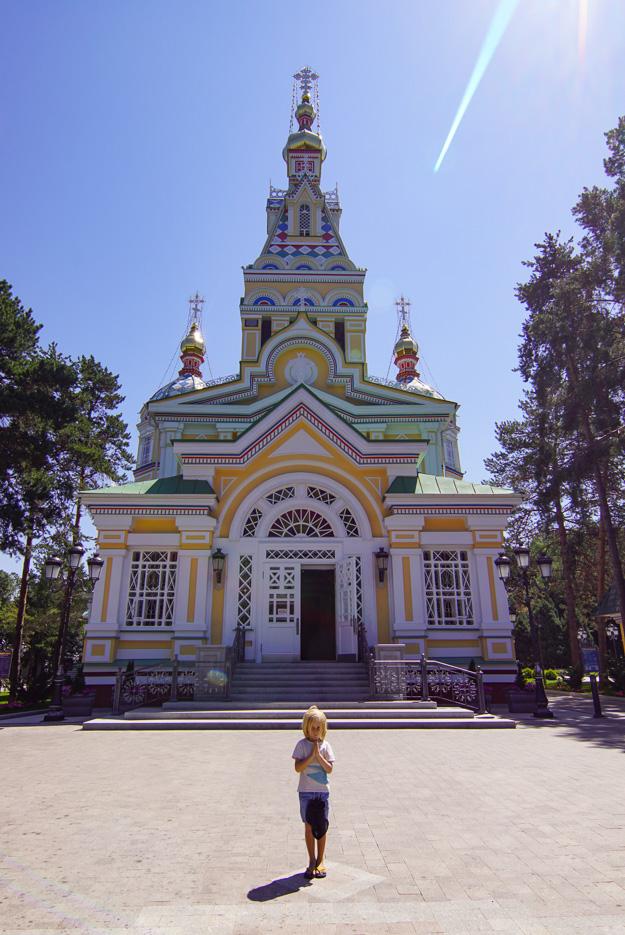 Luk steht mit gefalteten Händen und gesenkten Kopf vor der orthodoxen Kathedrale. Diese ist frisch renoviert und strahlt in bunt bemalten Farben es ist strahlend schönes Wetter.