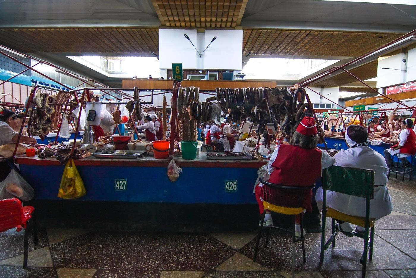 zu sehen ist die Fleisch Abteilung auf dem Green Basar in Almaty. Im Vordergrund sitzen zwei Verkäuferin auf Stühlen dahinter erstrecken sich die einzelnen Stände mit Nummern markiert und unzählige Würste, Fleischstücke und Tierköpfe werden angeboten.
