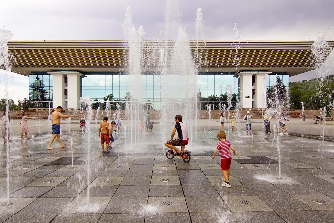 Vor dem Palast der Republik in Almaty befinden sich mehrere Springbrunnen. auf dem Bild ist zu sehen wie Paul auf Luk Kinderfahrrad durch die Wasser Fontänen radelt. Viele Kinder und Erwachsene springen durch die Wasserstrahlen.