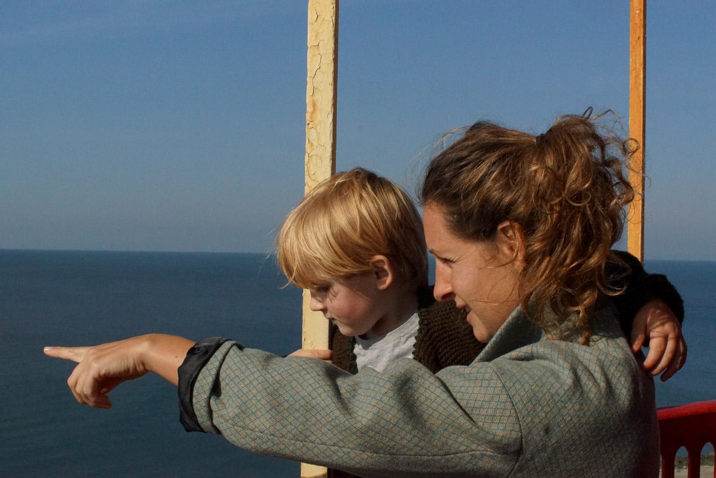 Zu sehen ist, wie Lea und Luk an der Brüstung des Leuchtturmes von Poti stehen. Lea zeigt mit der ausgestreckten Hand aufs Meer und Luk folgt ihren Blick.