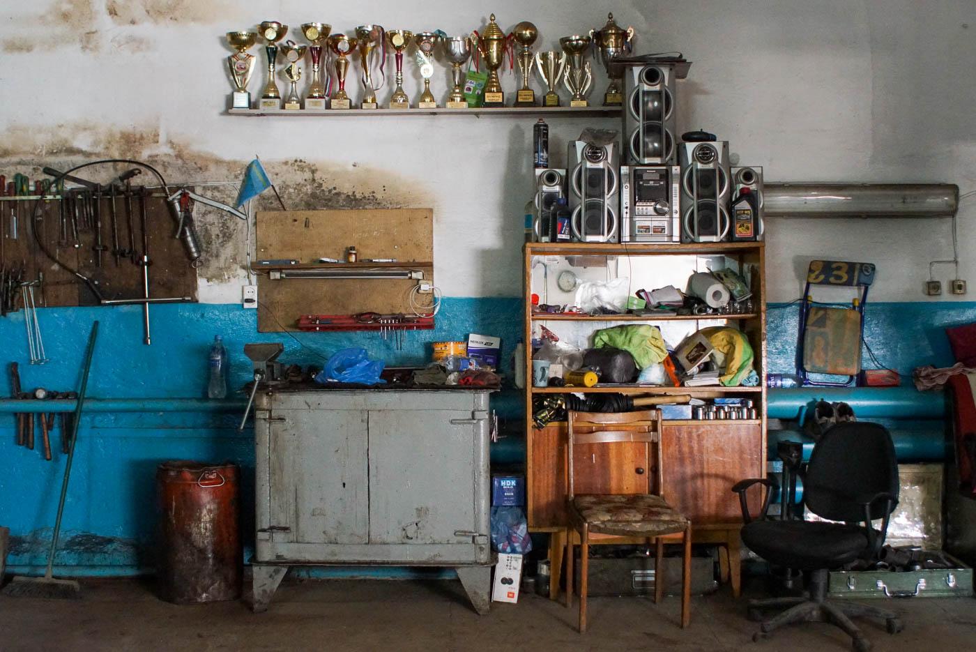 zu sehen ist die Band in einer Werkstatt in Pawlodar links hängen Werkzeuge an der Wand in der Mitte ist eine Stahl Kommode mit Schraubstock und Arbeitsfläche zu sehen darüber ist ein Brett mit vielen Pokalen von Autorennen angebracht. Rechts ist ein Regal mit großer Stereoanlage oben drauf und allerlei Krimskrams in drin zu sehen.
