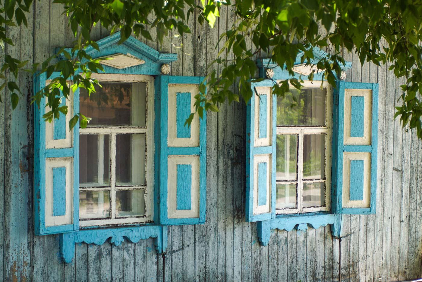 Zu sehen ist die die Wand eines traditionellen Holzhauses in Pawlodar. In der Wand sind zwei alte Fenster eingerahmt von Blau-Weißen Fensterläden mit wunderschön verzierten Rahmen.