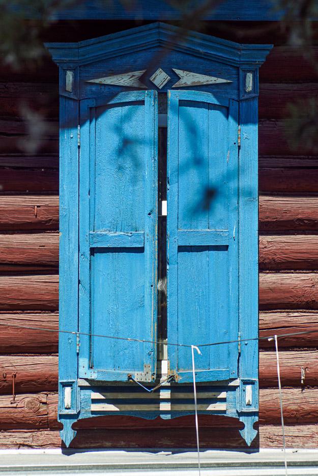 zu sehen ist ein traditionelles Blockhaus in Pawlodar im Zentrum des Bildes steht ein Fenster welches mit blauen Holz Fensterläden verdeckt wird der Rahmen ist kunstvoll gestaltet.