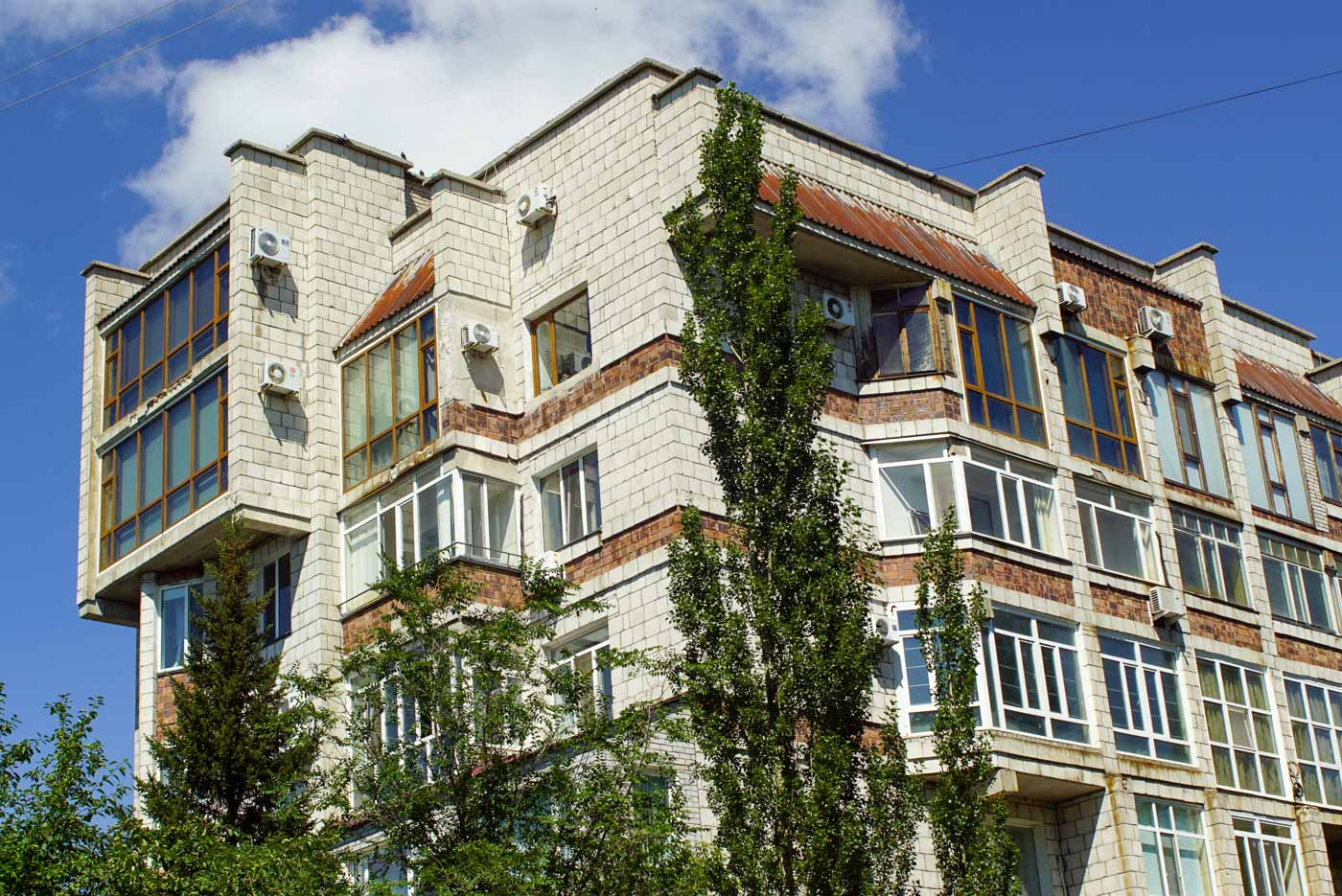 zu sehen ist ein verschachteltes Gebäude mit vielen Erkern und großen Fenstern davor erheben sich grüne Bäume. Der Himmel ist strahlend blau.