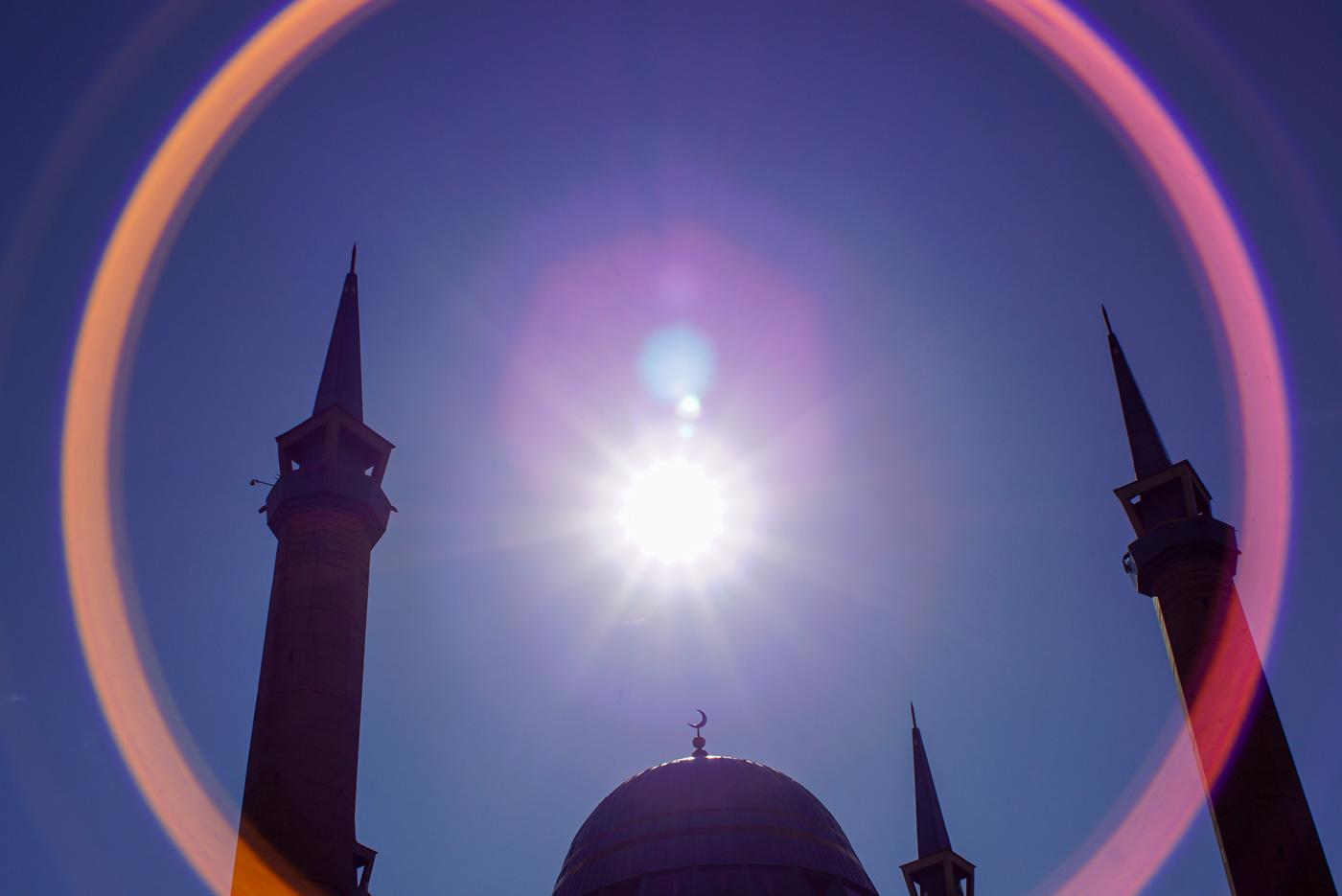 zu sehen sind die vier Minarette und die Kuppel der neuen Moschee in Pawlodar genau im Zentrum darüber erstrahlt die Sonne.