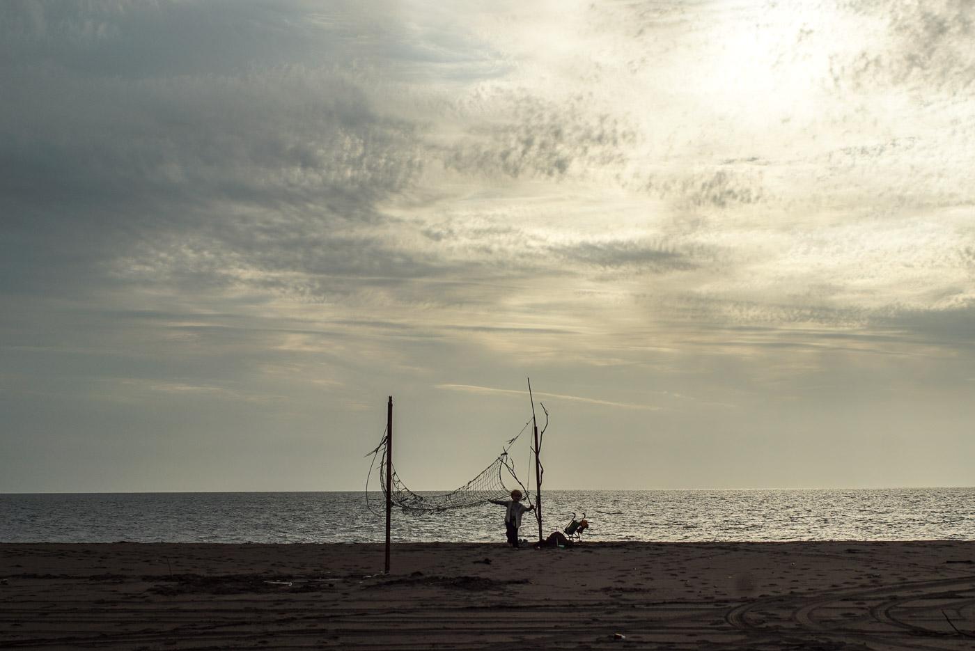 Zu sehen ist ein Sandstrand, mit ruhiger See im Hintergrund und Schäfchenwolken durch die die Sonne bricht. Am Strand ist ein selbstgemachtes Volleyballnetz aus großen Holzstücken und einem alten Fischer Netz das durchhängt zu erkennen. Luk steht mit seinem Puppen Kinderwagen daneben.