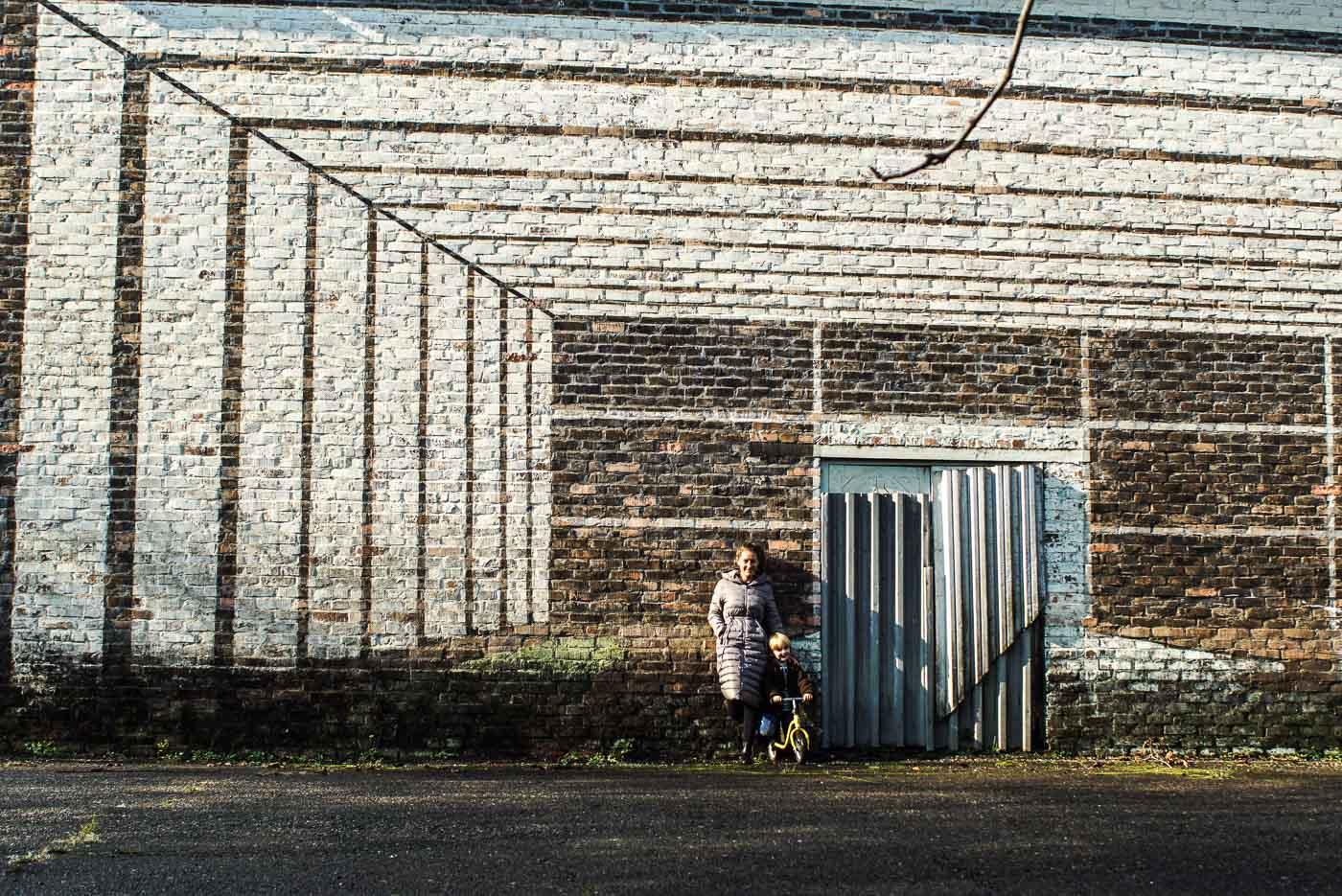 Lea steht neben Luke der auf seinem Laufrad sitzt neben einer grauen Tür. Auf die Backsteine des Gebäudes wurde mit weißer Farbe perspektivisch der Innenraum einer Halle gezeichnet.