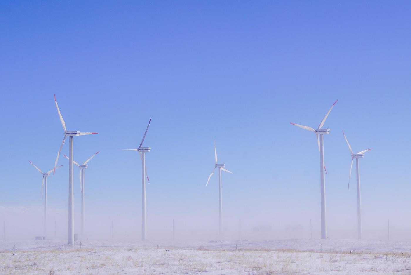 Zu sehen ist eine vom Frühnebel schneebedeckte Steppe. aus dem Nebel erheben sich 7 riesige Windräder.