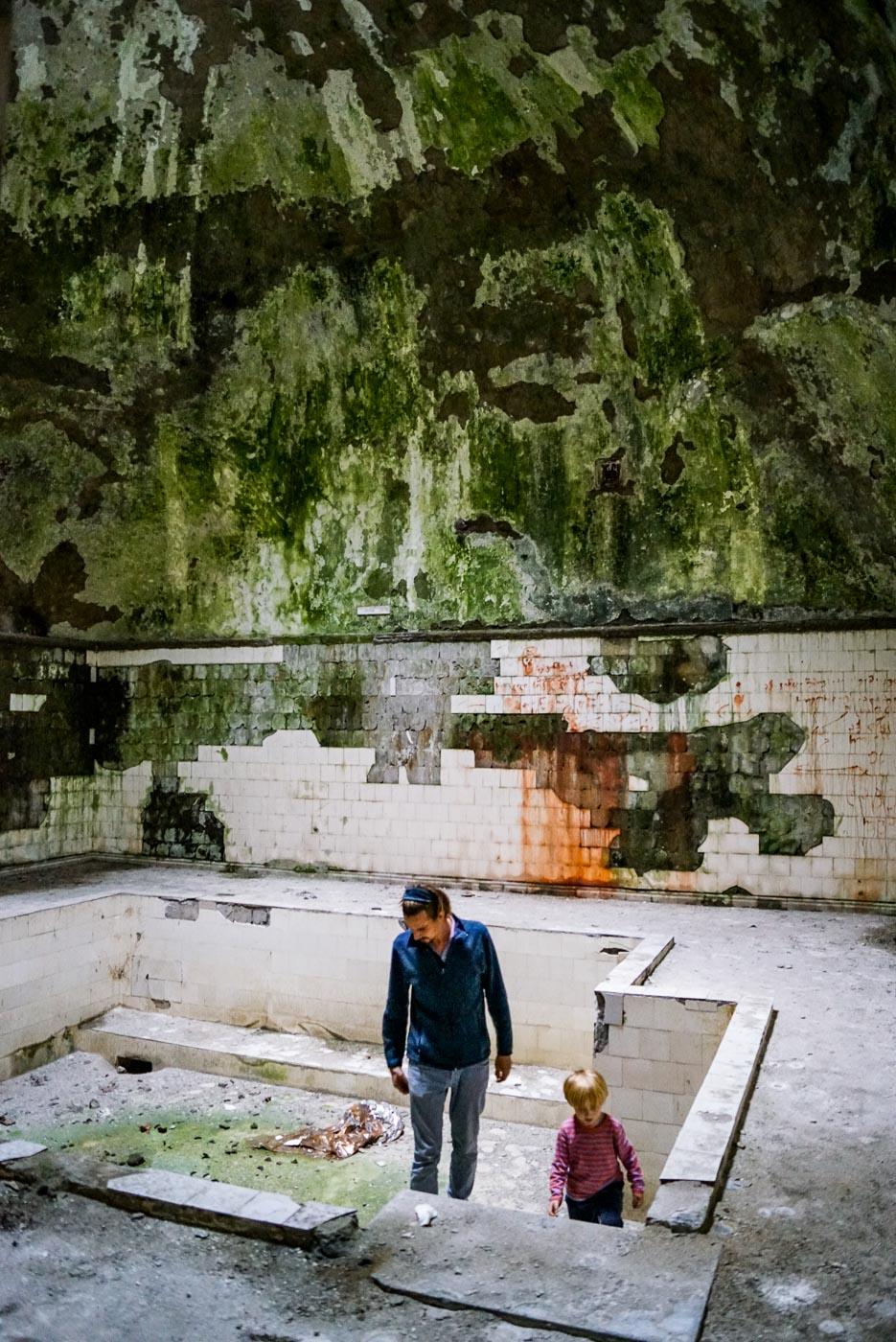 Luk und Paul stehen in einem leeren Swimmingpool in einem der verlassenen Sanatorium. Die Kacheln bröckeln von den Wänden dahinter scheint zeigt sich Moos ebenso istdie gewölbeartige Decke ist tief grün.