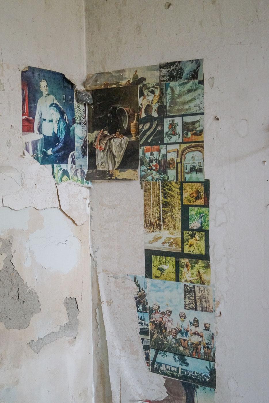 Zu sehen ist die Ecke eines Raumes innerhalb eines der Sanatorien. Der Putz bröckelt von der Decke von der Wand jedoch hängen noch einige Poster von von den ehemaligen Bewohnern an der Wand. Pionieren Landschaftsaufnahmen oder klassischen Gemälden.
