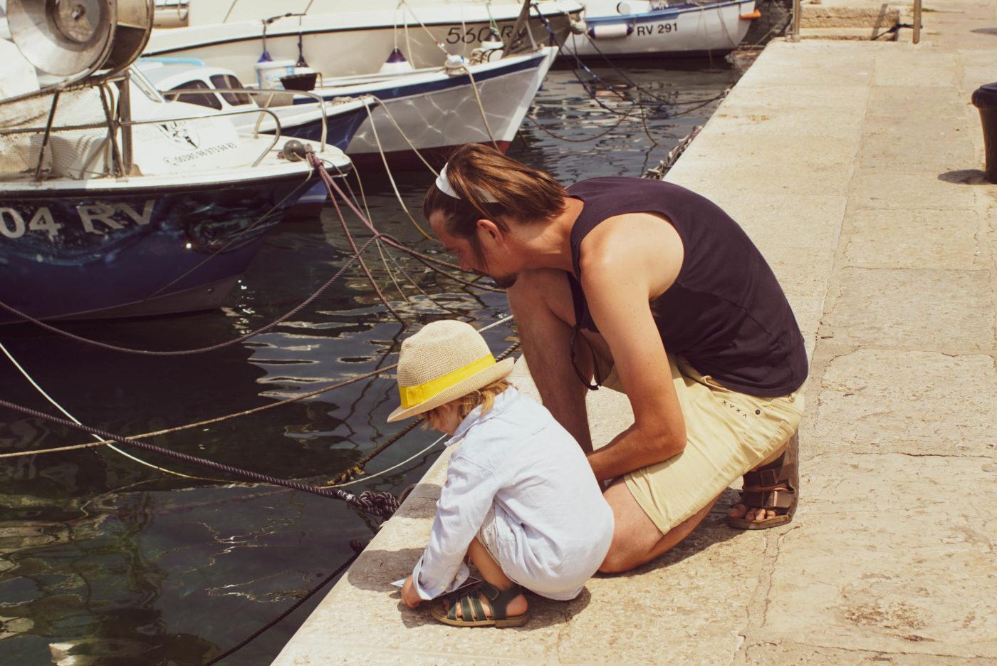 Paul und Luk hocken an der Hafenkante und betrachten Fische im kristallklarem Wasser. Im Hintergrundsind kleine Motorboote zu sehen.