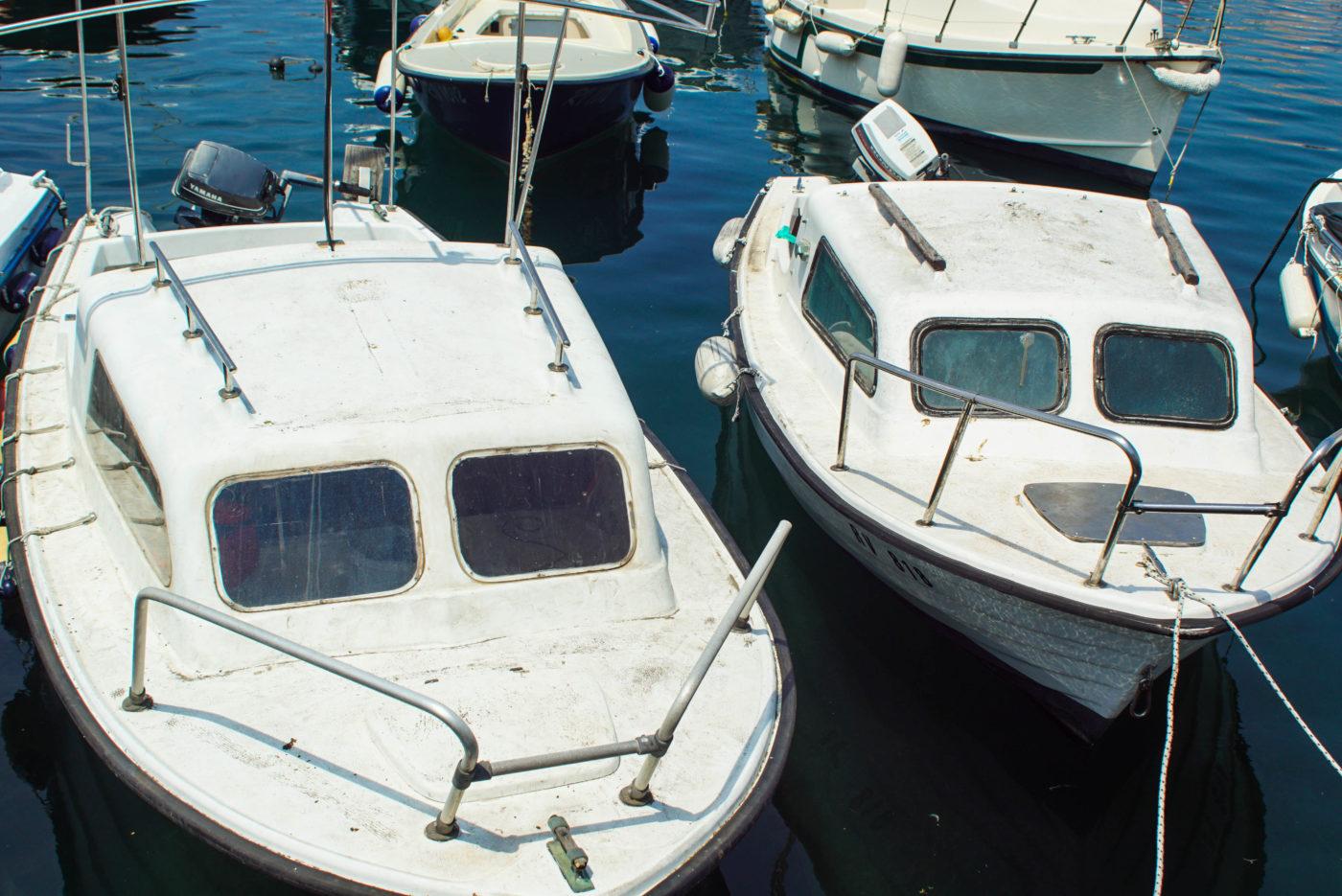 Es sind zwei kleine weiße Motorboote zu sehen welche dicht beieinander in tief dunkel blauem Wasser im Hafen fest gemacht sind.