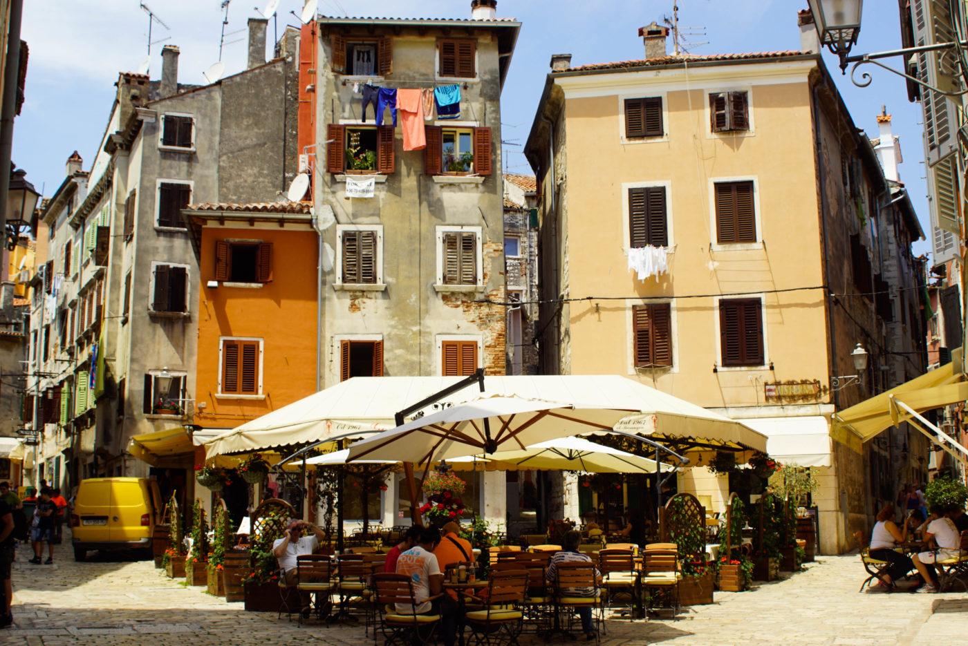 Es ist ein typischer mediterraner Platz zu sehen. Im Vordergrund sind große Sonnenschirme und darunter genießen Leute die Atmosphäre. Drei schmale Gassen führen sternförmig zwischen drei und vierstöckigen Häusern weg.