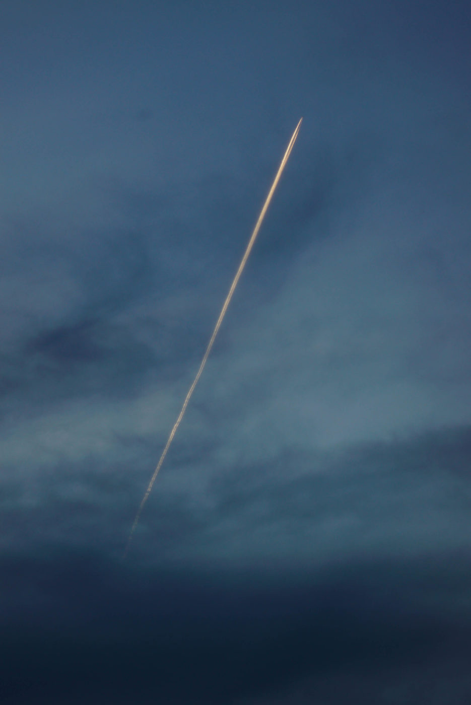Die Sonne ist schon untergegangen, hoch am Himmel Fliegt ein Flugzeug dessen Kondensstreifen noch von der Sonne beleuchtet wird