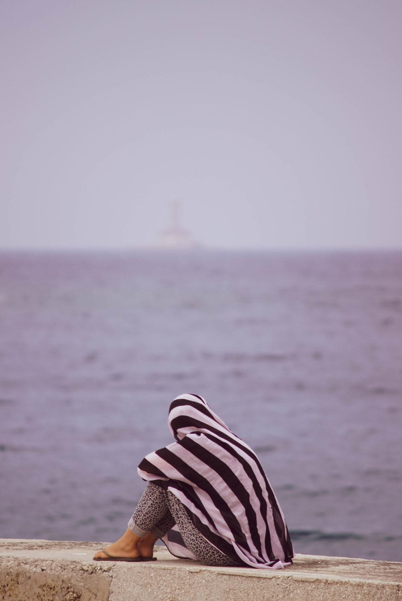 Lea sitzt auf einer Mole blickt aufs Meer und hat sich ein Tuch um Kopf und Körper gelegt