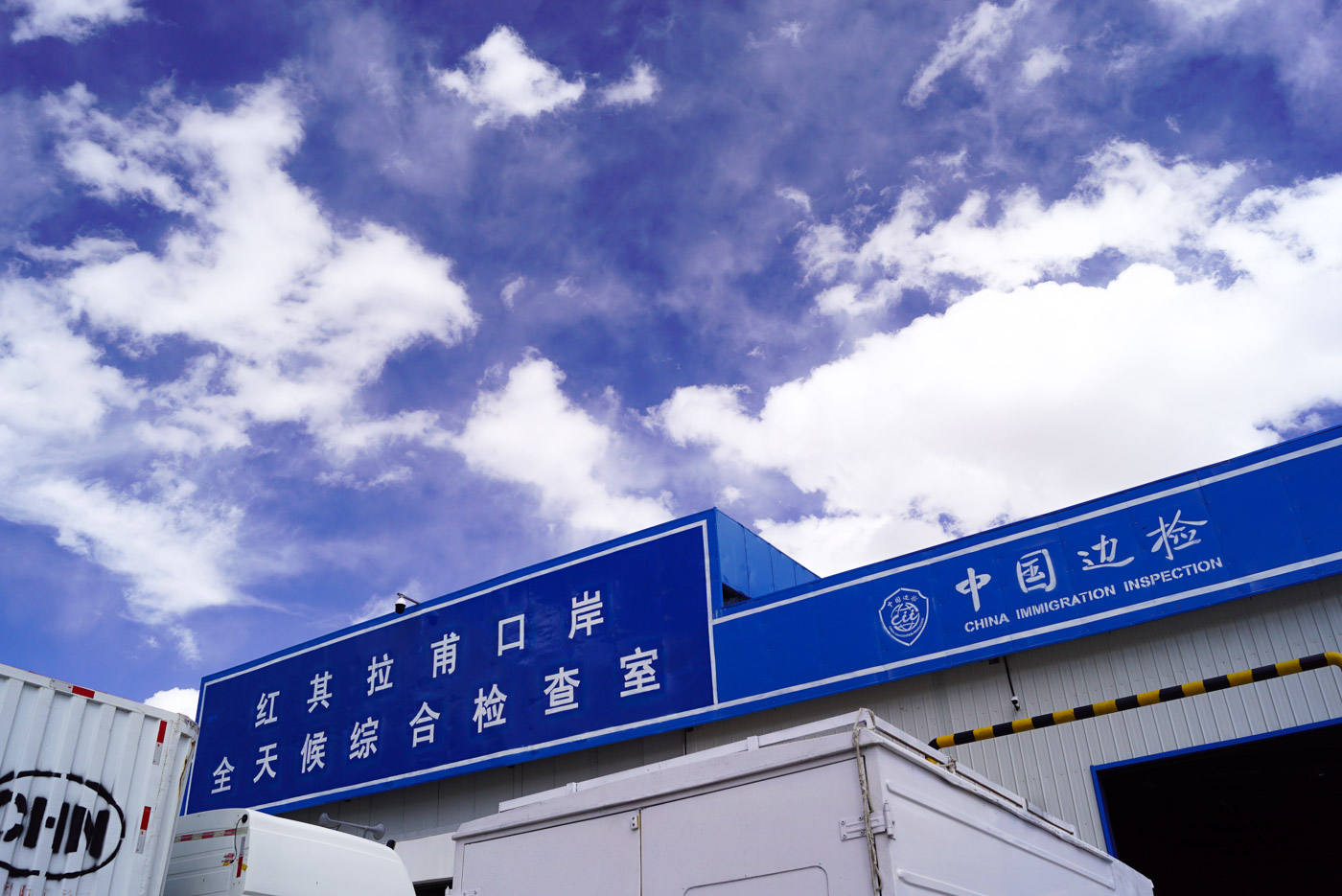 """Zu sehen ist das Kontrollgebäude am Khunjerab Pass, auf dem blauen Dach sind chinesische Schriftzeichen in der Mitte zu sehen rechts davon steht """"China Immigration inspection""""."""