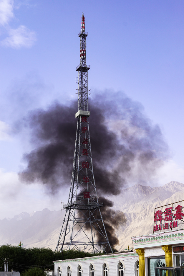 Zu sehen ist ein hoher Funkmast der die Form des Eiffelturms hat. Dahinter erhebt sich eine schwarze Rauchwolke in den Himmel diese bildet einen wundervollen Kontrast zu dem blauen Himmel mit Bergen im Hintergrund.