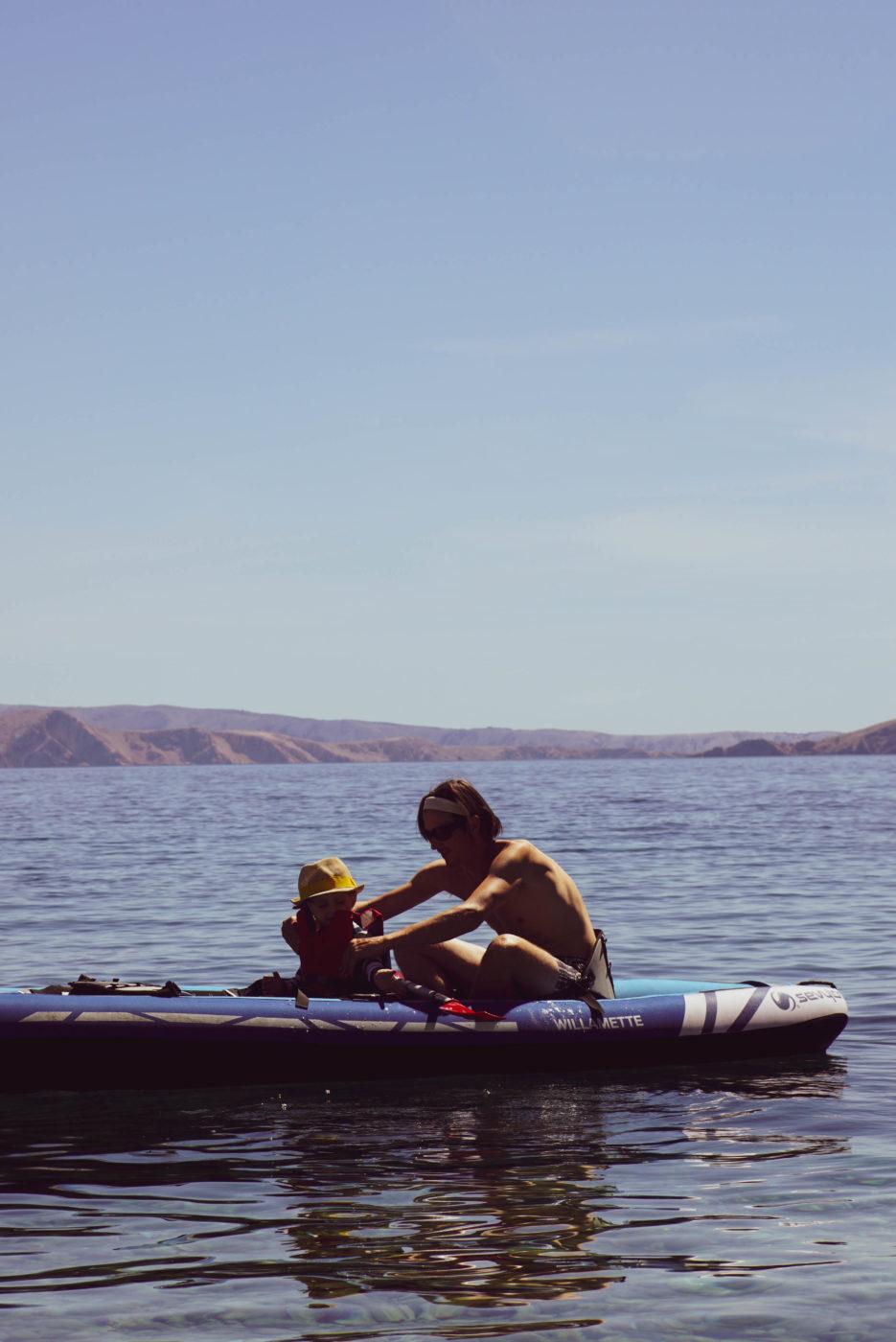 Paul und Luk padeln in einem Luftkajaküber spiegelglattes Wasser. Im hintergrund ist die Küste einer Insel zu sehen