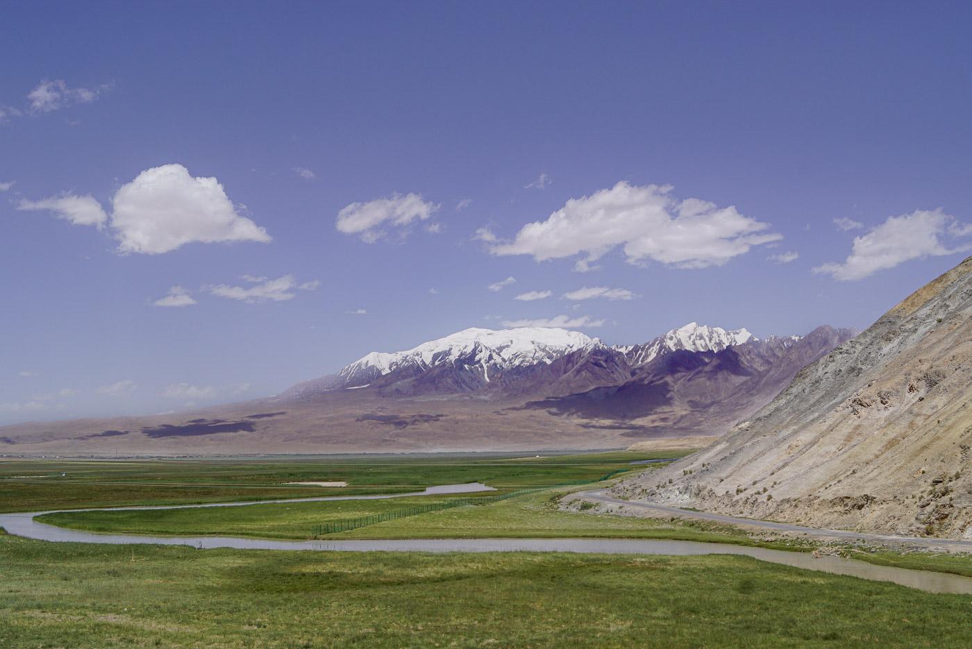 Unter einem Blau-Weißen Himmel erhebt sich ein Berg mit 7000 m Höhe an seinem Fuß erstreckt sich eine grüne Ebene die von einem Fluss schlängeln durchzogen wird.