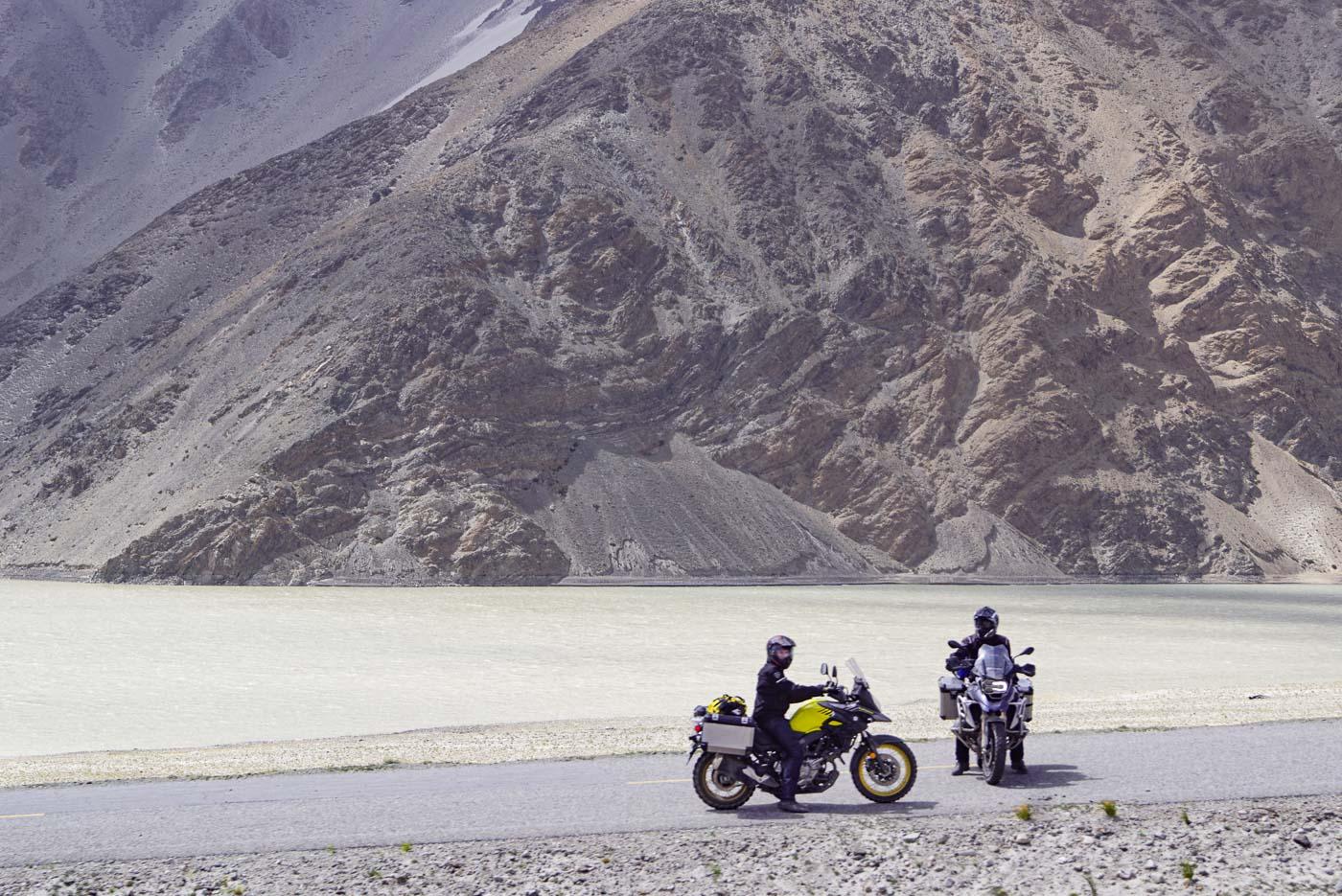 Johann und Mikael sitzen auf ihren Motorrädern und blicken in die Kamera dahinter ist ein brauner See zu sehen im Hintergrund erheben sich schroffe Berg Formationen.