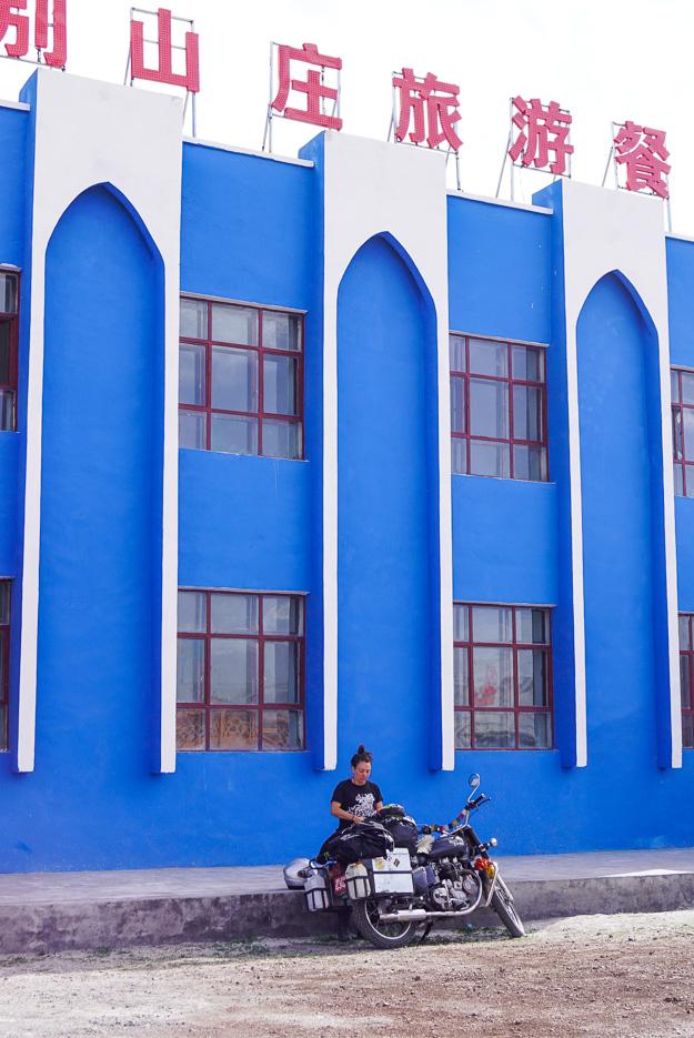 Zu sehen ist ein blaues zweistöckiges Gebäude es wird gekrönt von roten chinesischen Schriftzeichen Punkt davor steht Charlotte's mit ihrer Royale Enfield und macht sich bereit zum Essen zu gehen.