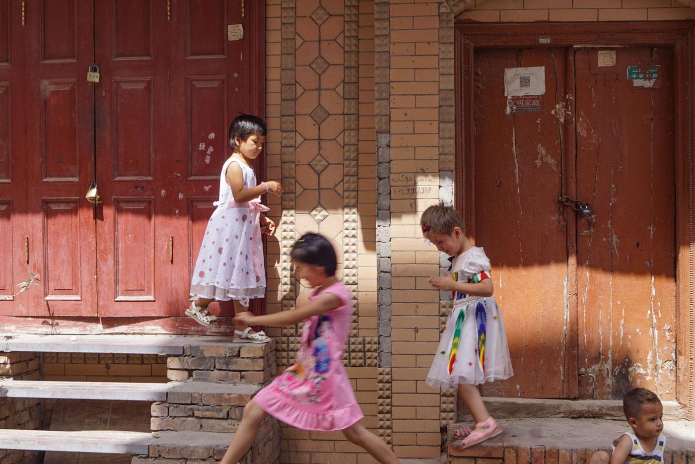 Zu sehen sind drei Mädchen die im Kreis über Treppen springen die zu zwei Eingangstüren führen.