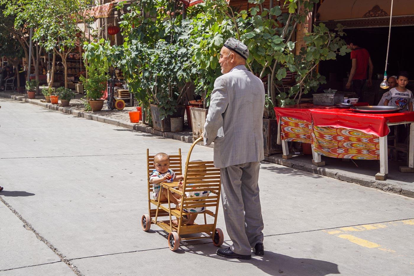 Zu sehen ist ein alter Mann im grauen Anzug mit uiguren Mütze. Er schiebt einen selbstgebauten zweisitzigen Kinderwagen bei dem sich zwei kleine Zwillinge durch einen kleinen Tisch getrennt gegenübersitzen.