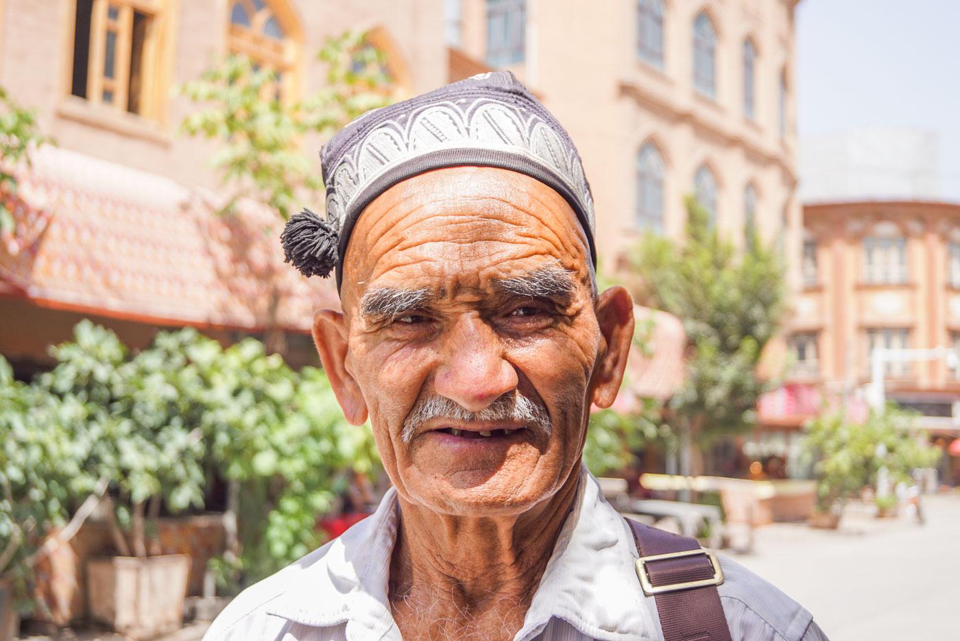 Eine Portraitaufnahme eines ca. 60 Jahre alten Uiguren. Er hat eine traditionelle graue Mütze auf dicke graue Augen braunen und einen grau weißen Schnurrbart.