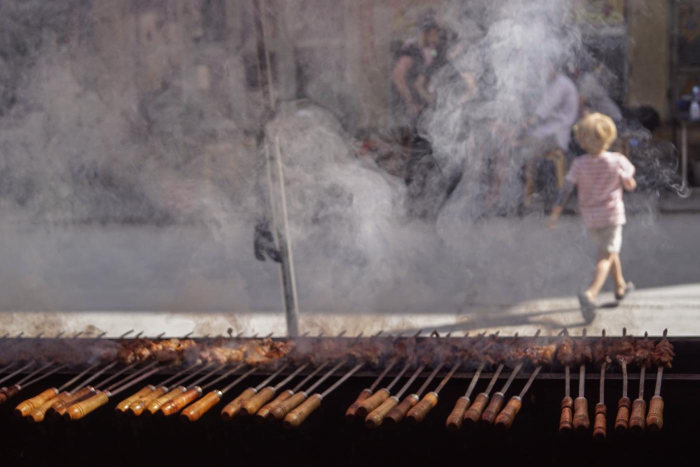 Im Vordergrund sind auf einem länglichen Grill ca 30 Schaschlikspieße zu sehen und dampfen steigt auf. Durch den Rauch sieht man im Hintergrund Luke über die Straße laufen.