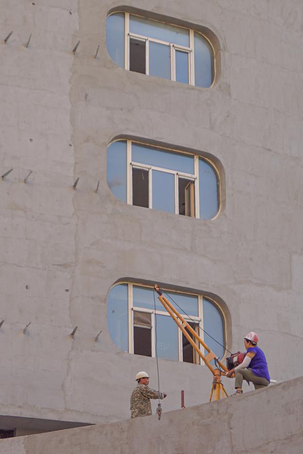 Zu sehen ist ein Teil eines Gebäudes und davon drei Stockwerke mit ovalen Fenstern vorne auf einem Absatz stehen zwei Bauarbeiter. Der eine bedient einen kleinen Kran und der anderen scheint ihm Anweisungen zu zu rufen.