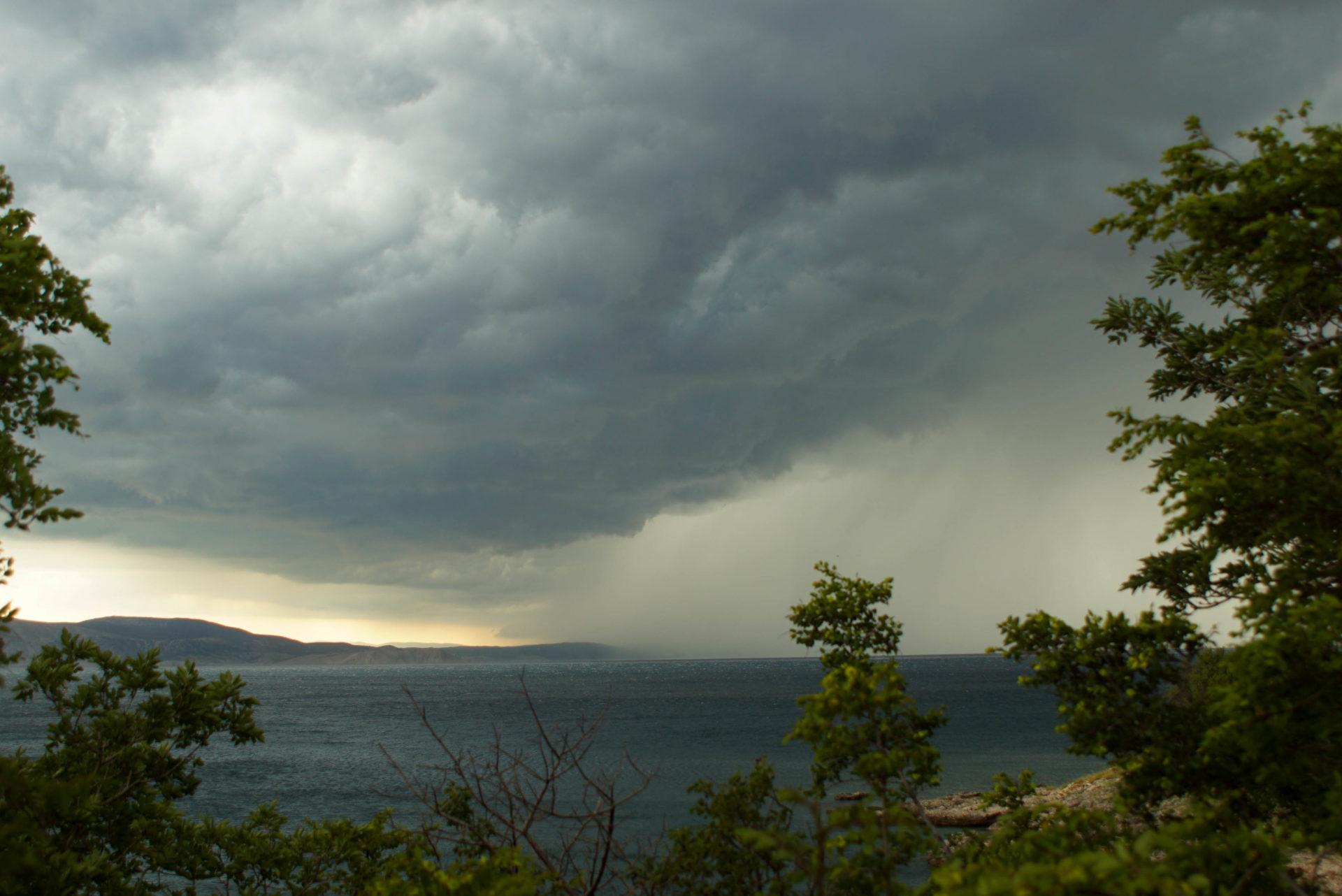Ein Blick auf die Bucht von Senj. Der Himmel ist mit Sturmwolken verhangen. In der linken Hälfte des Bildes ist die sicht Klar umd es ist die Küste der Insel Krk zu sehen. Die rechte Hälfte wird von einer weißen Sturmwand eingenommen.