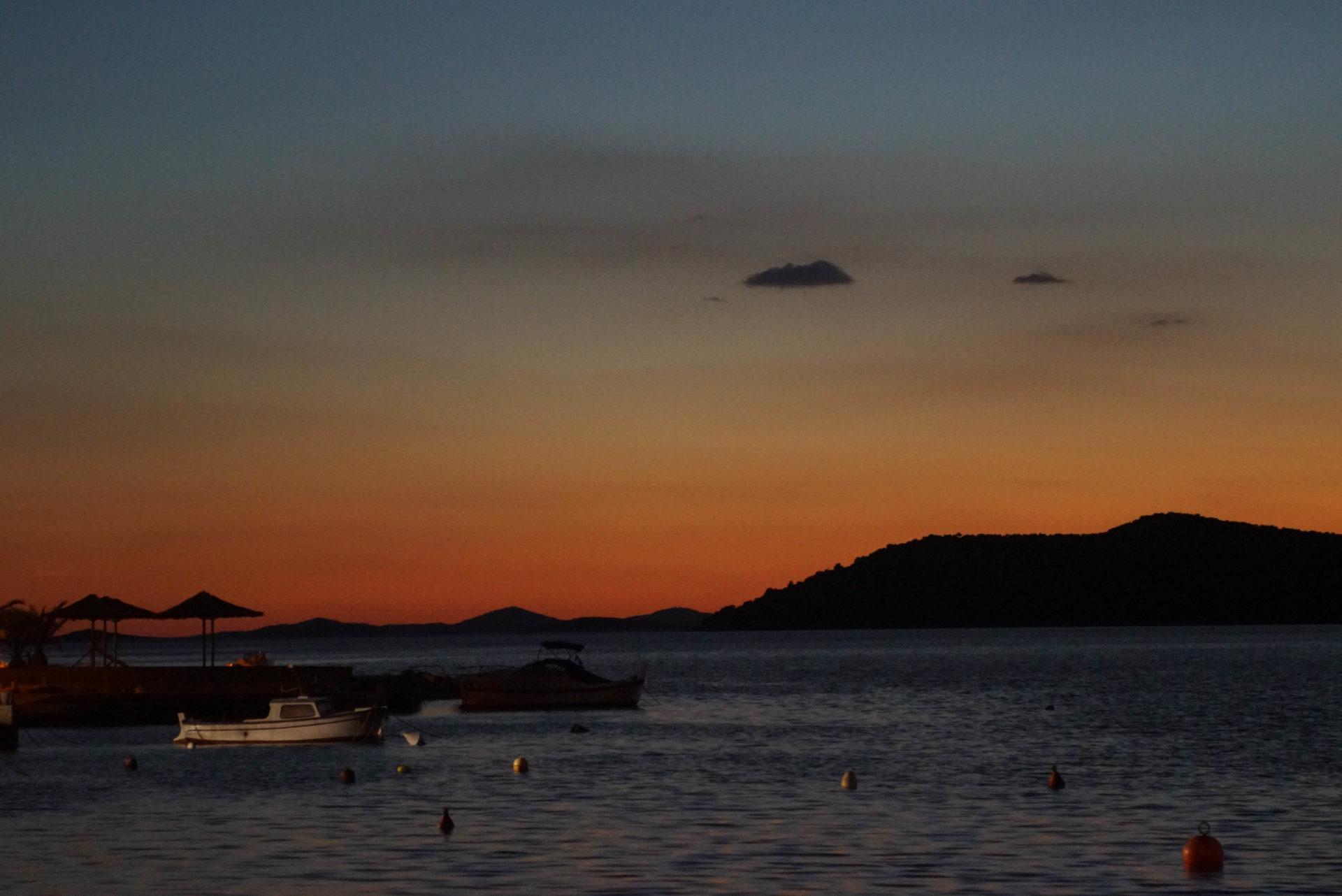 Die Sonne ist untergegangen und der Himmel färbt sich von blau bis tief rot zum Horizont. An der rechten Seite ist ein Berg zu sehe. Im Vordergrund links ist ein Pier mit Sonnenschirmen und zwei Booten zu sehen.