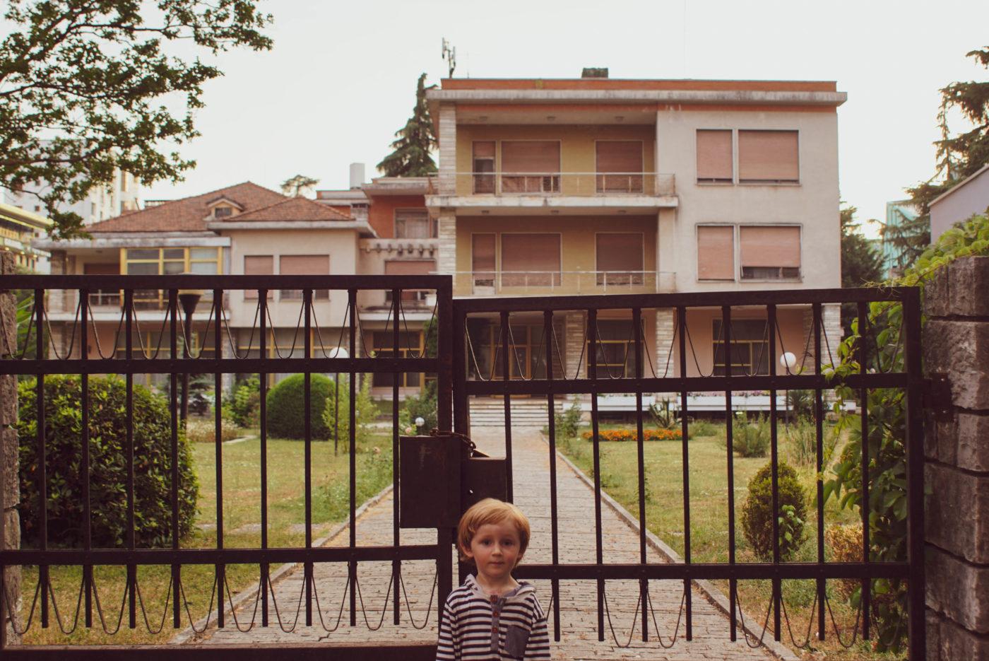 Zu sehen ist wie Luk vor dem Tor zu Hoxha´s Haus steht