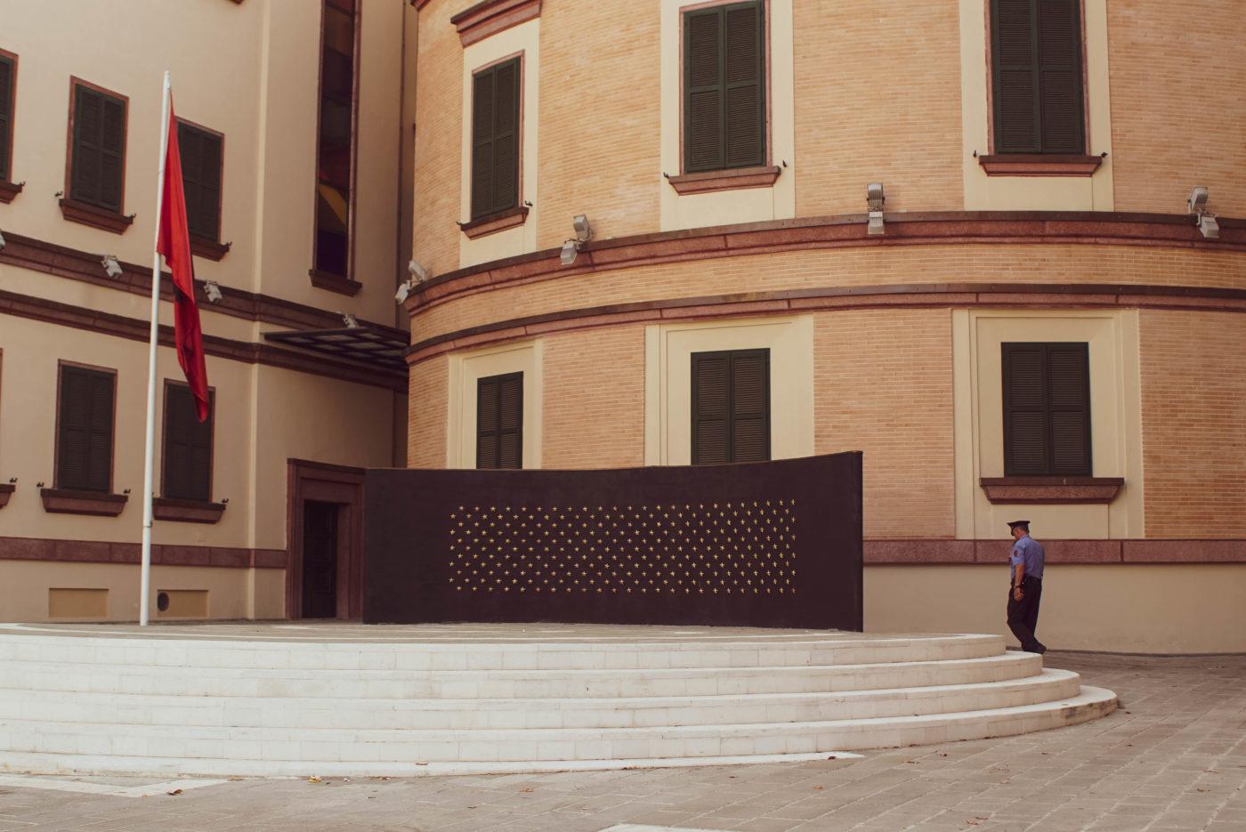 Eine schwarze Wand mt ca. 100 kleinen goldenen Sternen ist auf einem runden Podest zu sehen. Im Hintergrund läuft ein Wachmann vor einem der Regierungsgebäude im Zentrum von Tirana