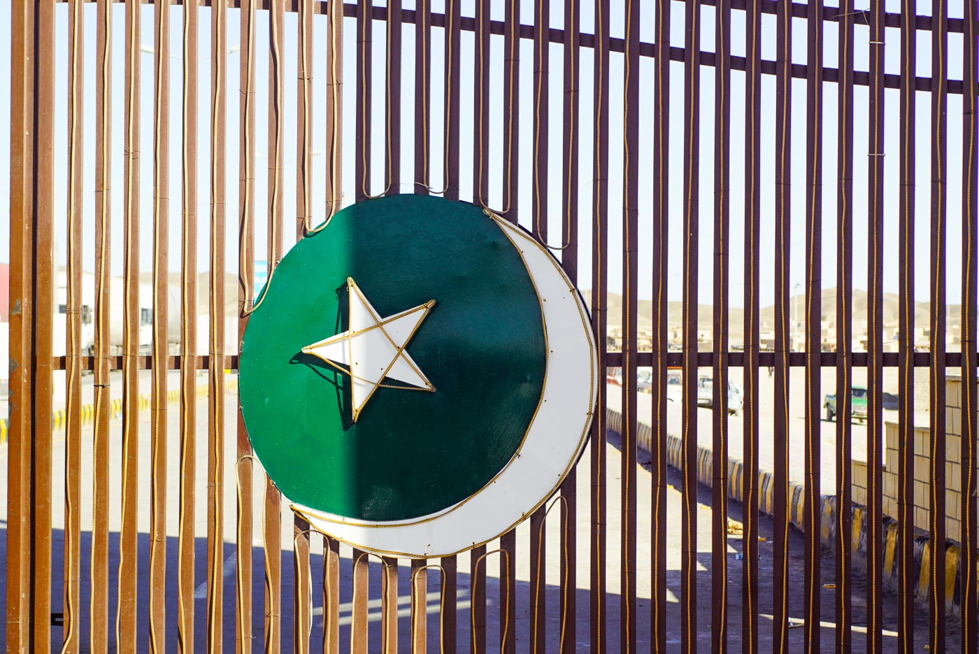 Zu sehen ist das Grenz Tor zwischen Iran und Pakistan. Es ist ein Metalltor auf dem ein grüner Kreis mit Mond und Stern zu sehen.