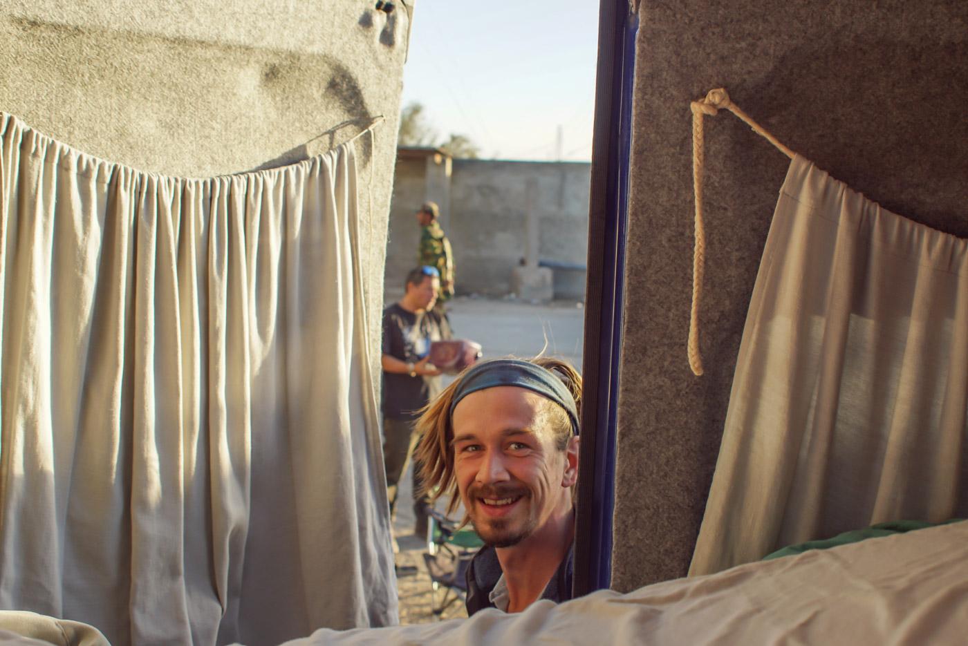 Paul öffnet gerade die Hecktür unseres Autos und schaut lächelnd hinein, im Hintergrund sieht man einen unserer Levie's in Camouflage vorbeilaufen