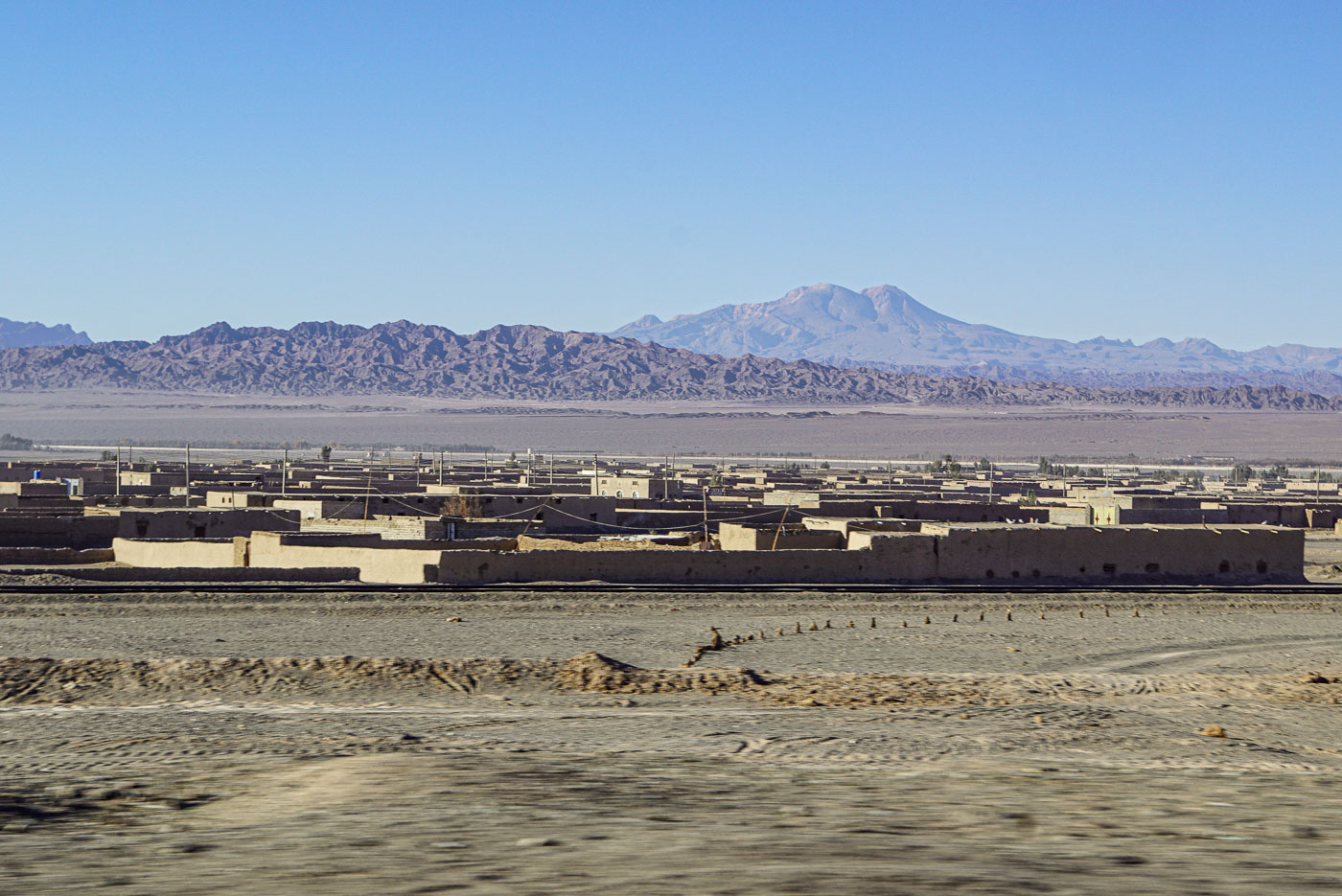 Im Vordergrund ist die vorbeiziehende Sand Landschaft zu sehen, dahinter schließt sich ein aus Lehmsteinen gebautes Dorf an. Im Hintergrund erheben sich schroffe Berge in unterschiedlichen Höhen.