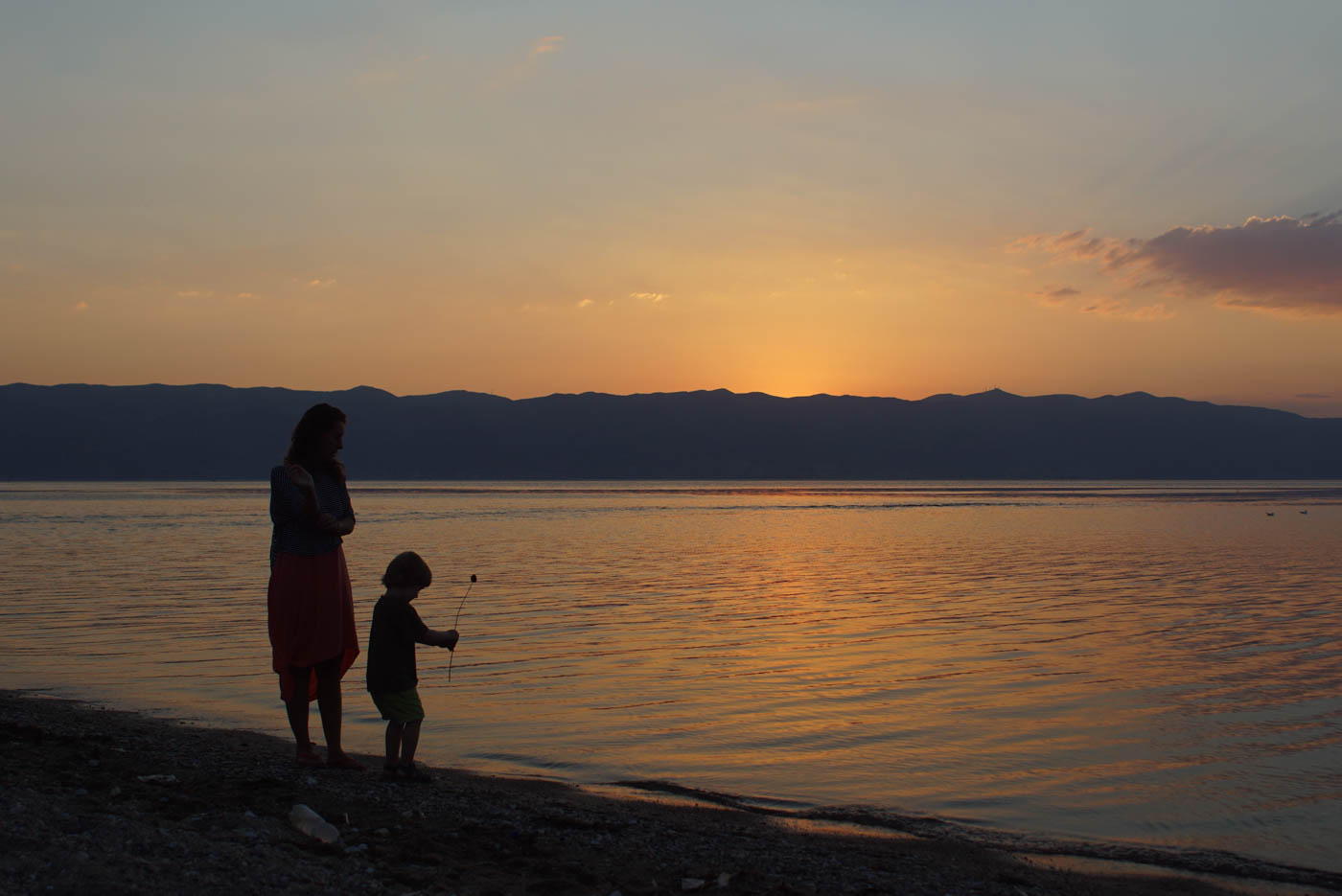 Sonnenuntergang am Ohridsee. Die Sonne ist bereits hinter den Bergen verschwunden, färbt aber noch Wolken und Wasser orange rot. Im Vordergrund steht Lea mit Luk und dieser hält eine Blume in der Hand und steht mit einem Fuß im Wasser.