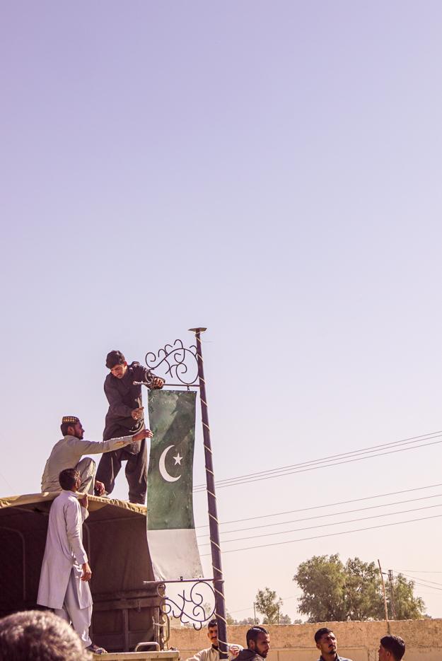 Zu sehen sind drei Männer die von einem Lastwagen aus an einem Laternenmast zur Verzierung die pakistanische Flagge anbringen.